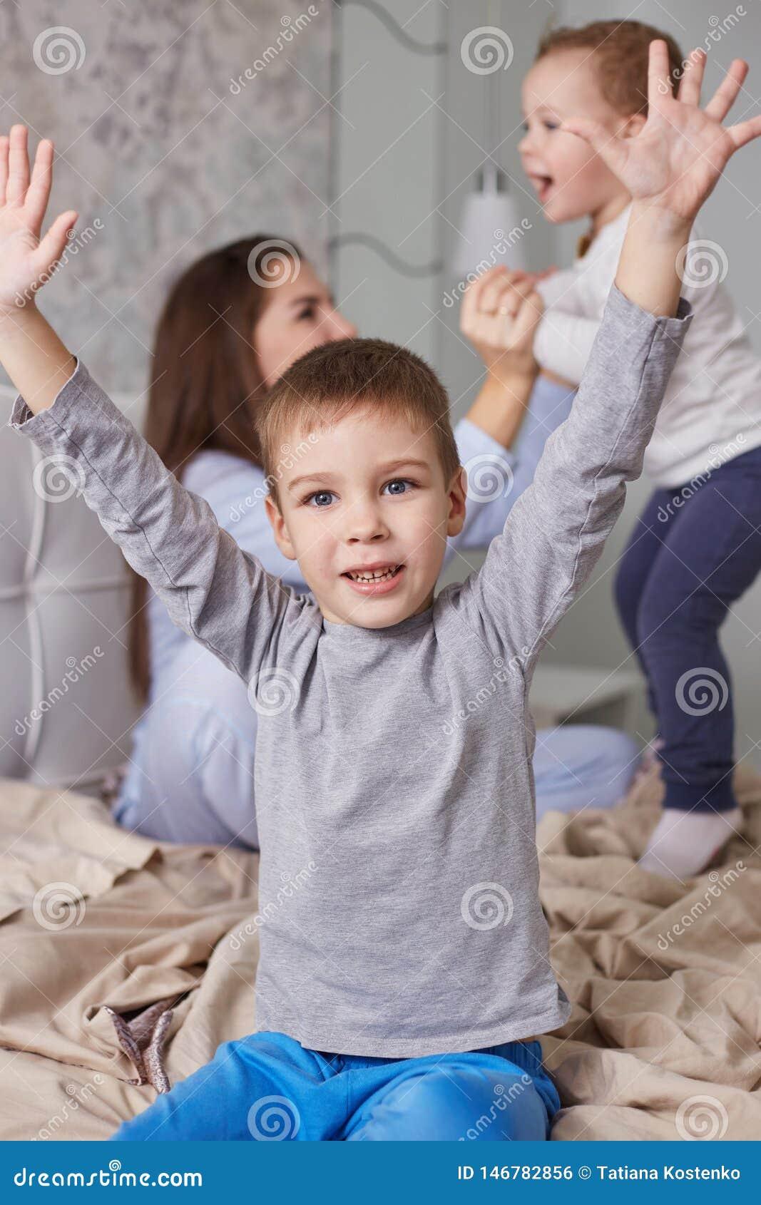 Due fratelli piccoli si divertono con la loro giovane madre vestita in pigiama blu-chiaro sul letto con la coperta beige in