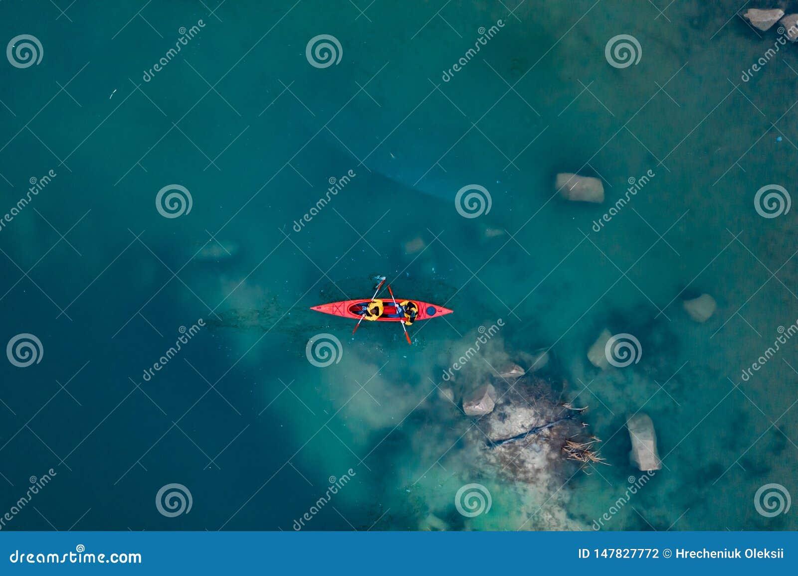 Due galleggianti atletici dell uomo su una barca rossa in fiume