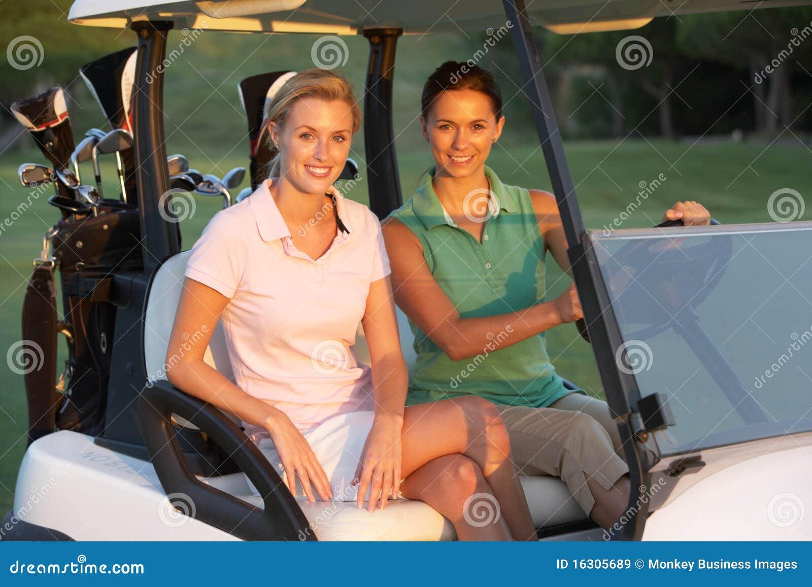 Due giocatori di golf femminili che guidano in Buggy di golf