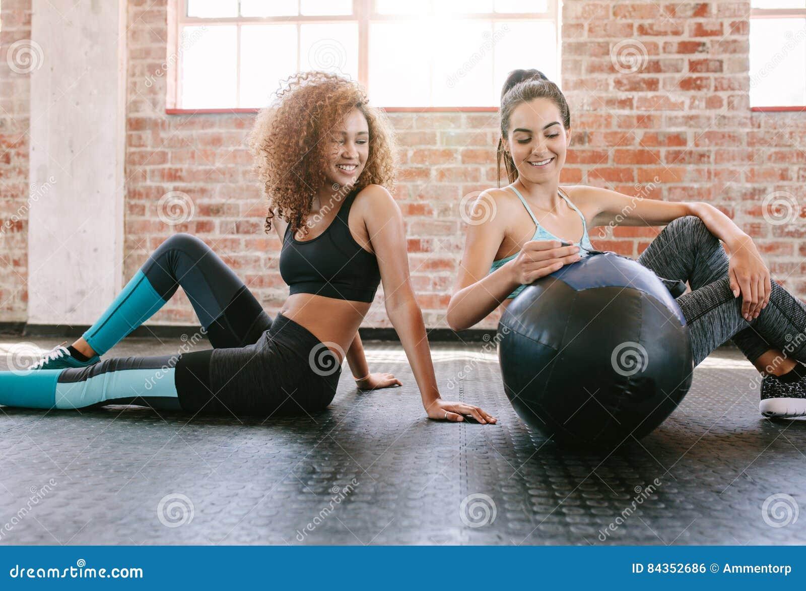 Due giovani amici femminili in palestra con palla medica