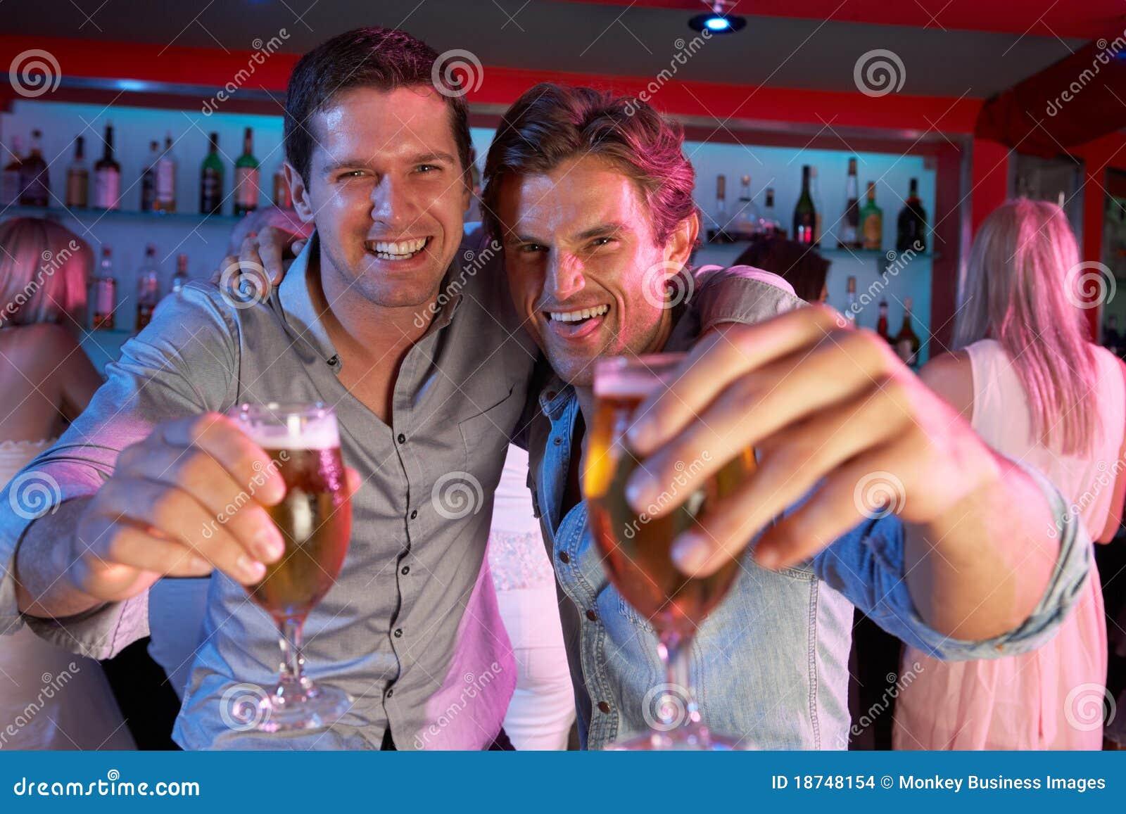 Due giovani che hanno divertimento in barra occupata