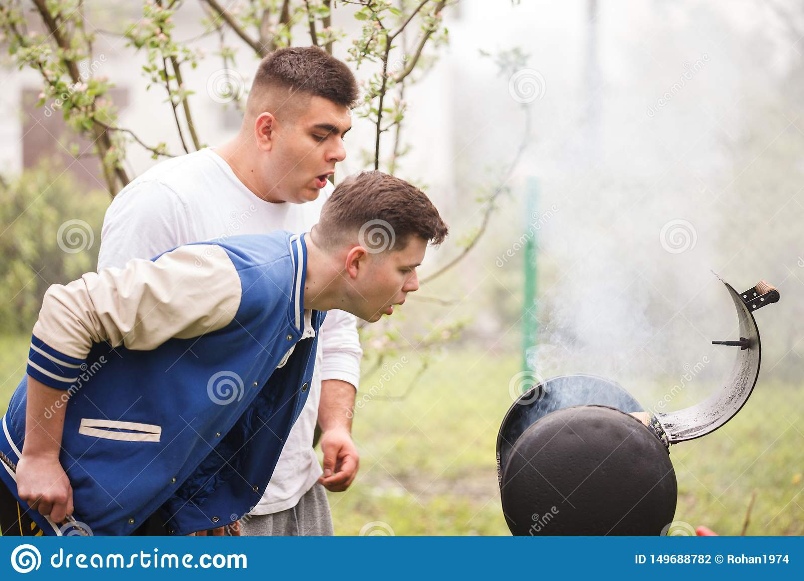 Due giovani che stanno vicino alla griglia del barbecue Accensione del fuoco all aperto