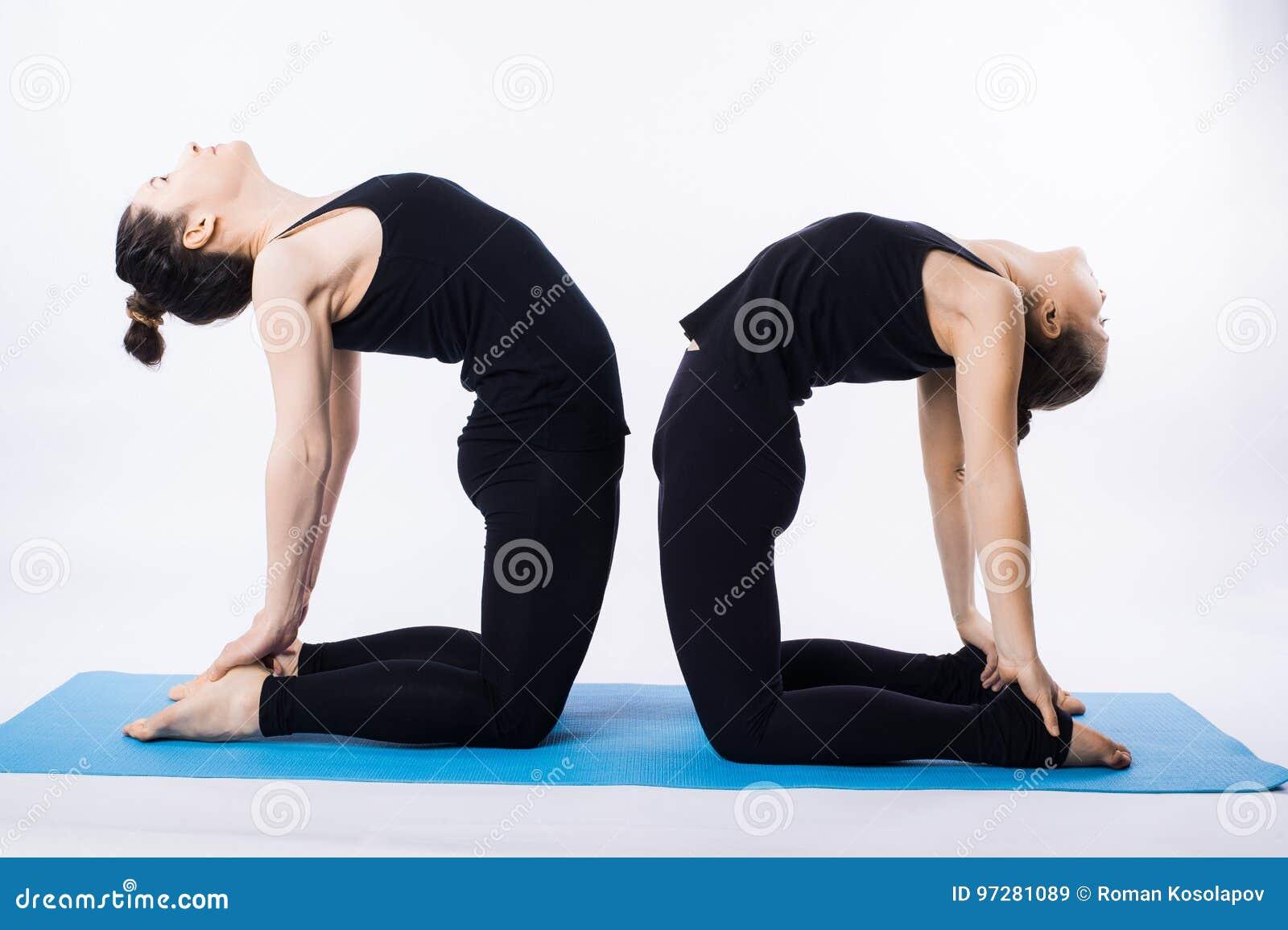 Due giovani donne che fanno l albero di asana di yoga posano Vrikshasana isolato su fondo bianco