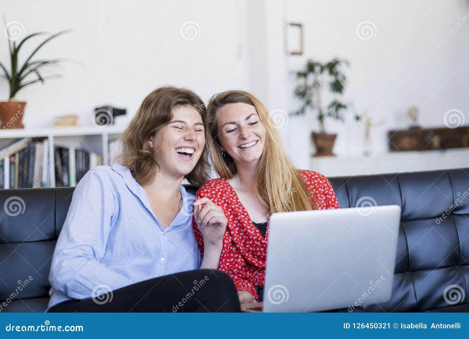 Due giovani donne che utilizzano computer mentre sedendosi sullo strato nel vivere