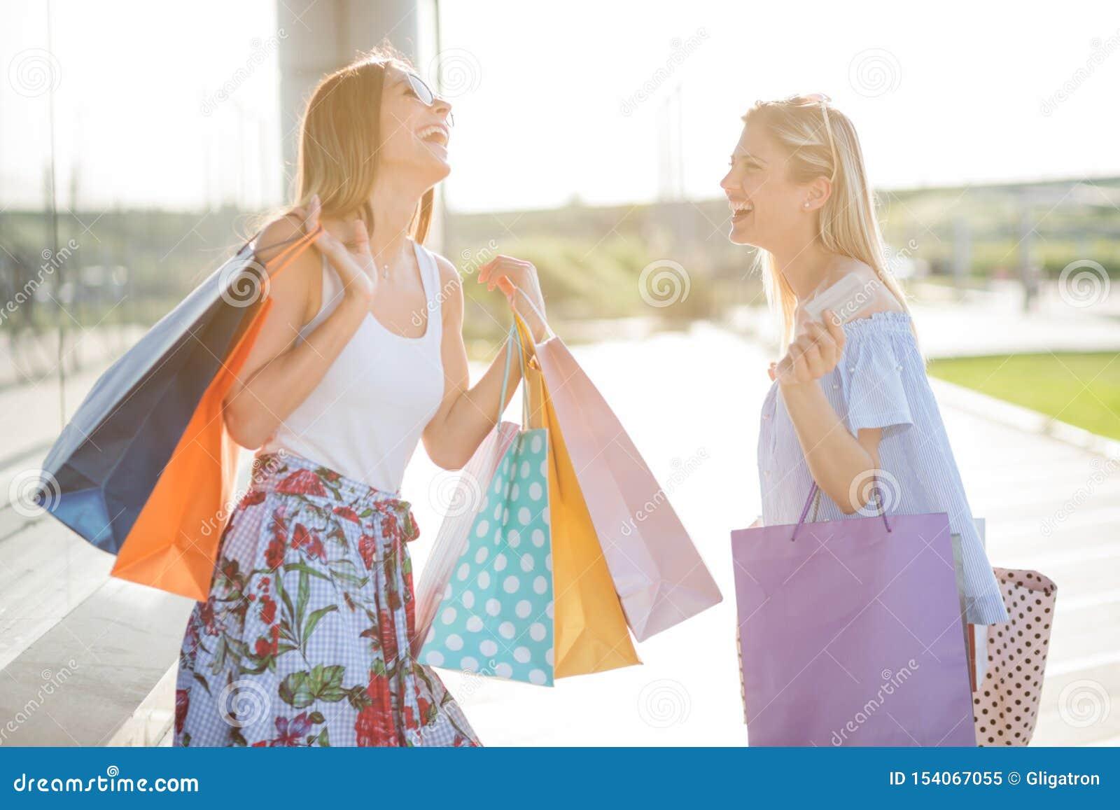 Due giovani donne felici sorridenti che ritornano dall acquisto