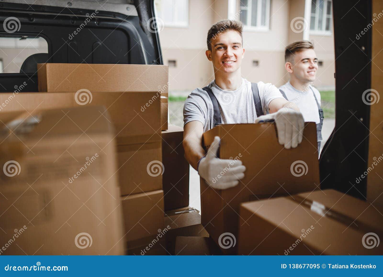 Due giovani lavoratori bei che portano le uniformi stanno stando accanto al furgone in pieno delle scatole r