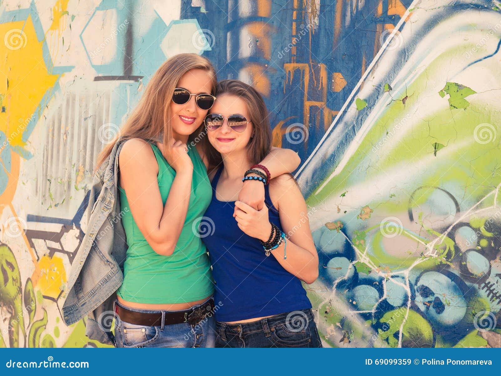 Due giovani ragazze teenager dei pantaloni a vita bassa che si divertono insieme i graffiti