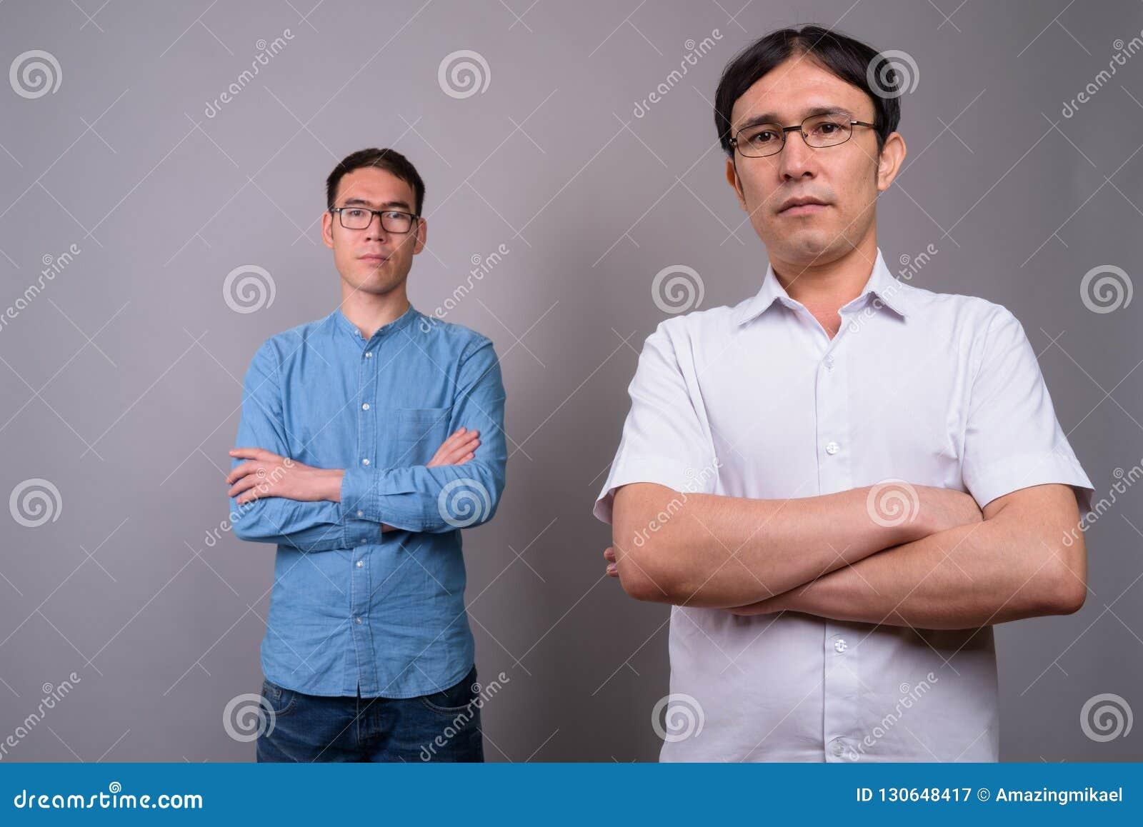 Due giovani uomini d affari asiatici che indossano insieme gli occhiali contro