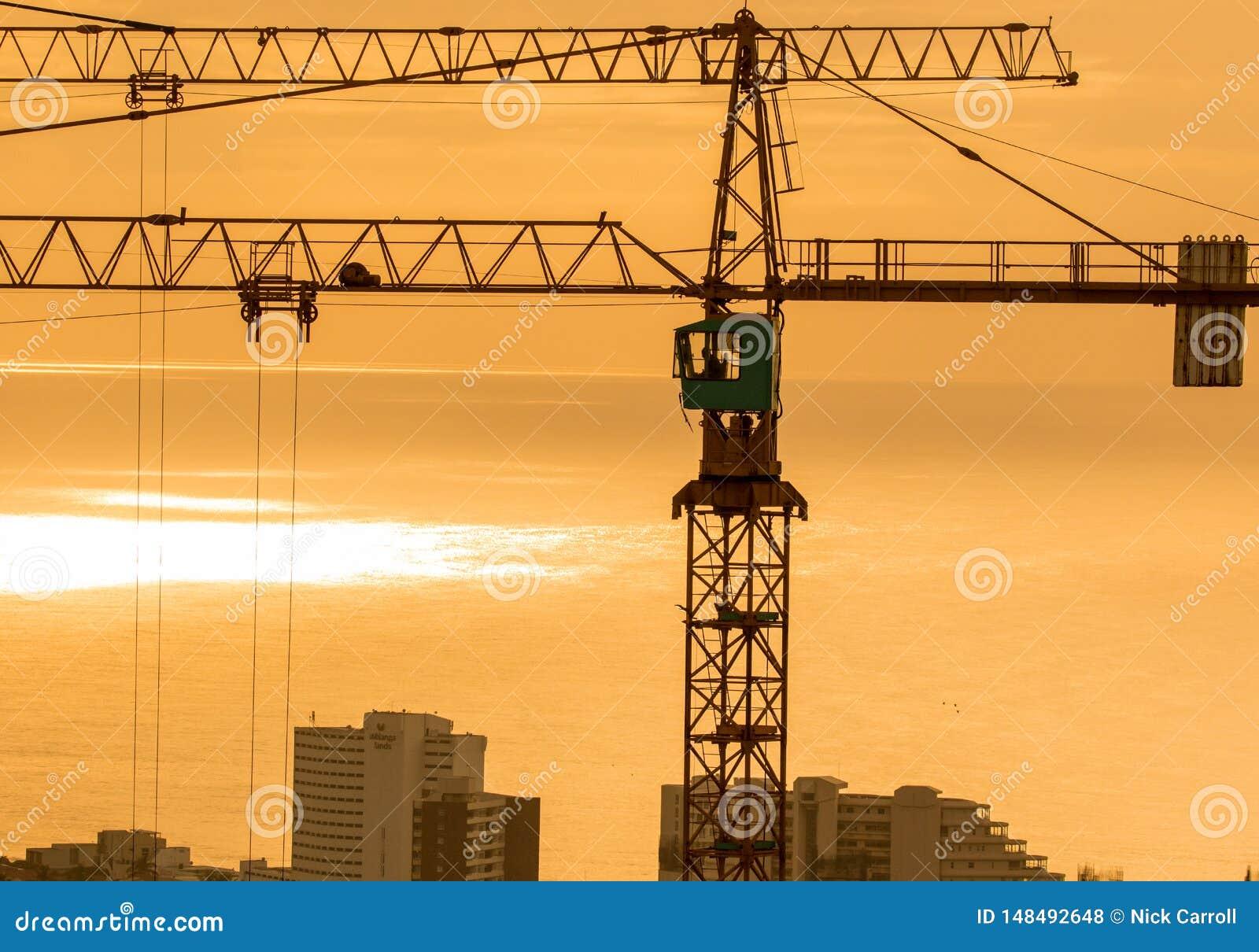 Due gru a torre della costruzione che dominano città costiera con il cielo arancio intenso all alba