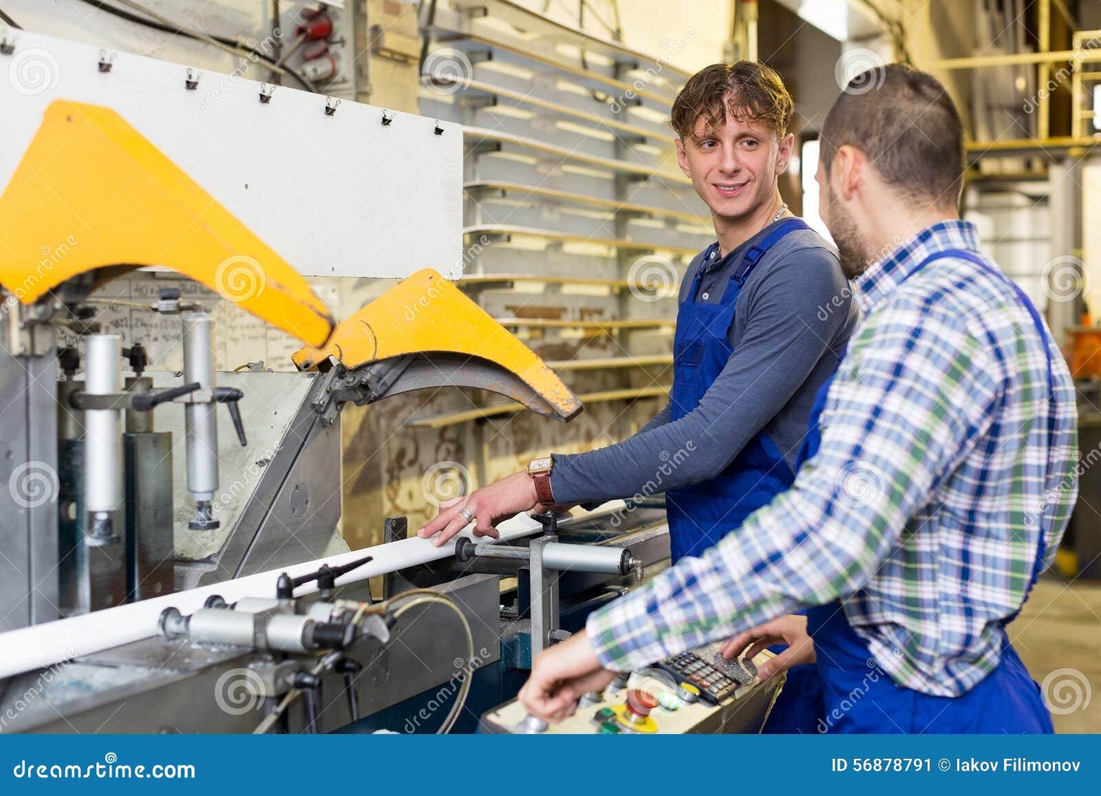 Due lavoratori che lavorano ad una macchina