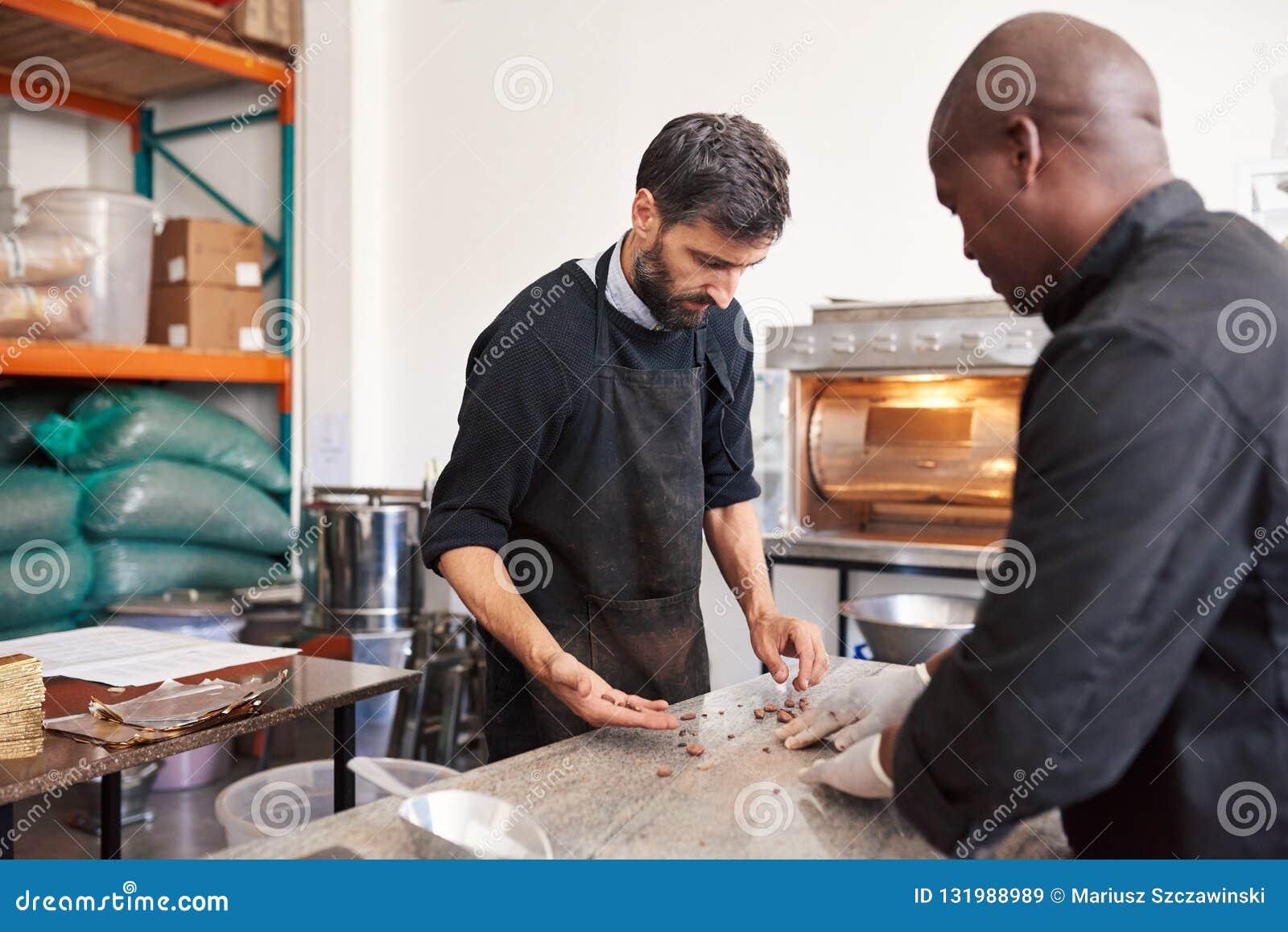 Due lavoratori che ordinano le fave di cacao in una fabbrica di fabbricazione di cioccolato