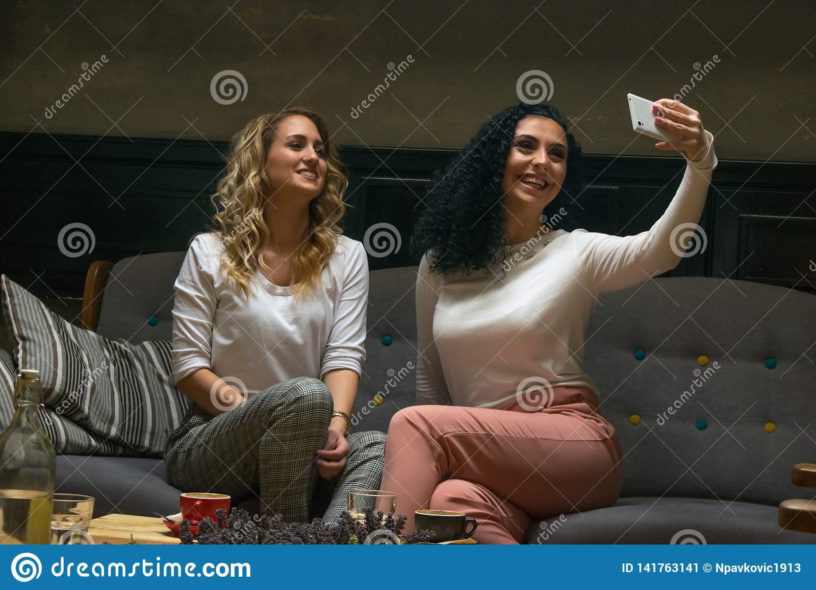 Due le migliori amiche stanno prendendo il selfie in caffè