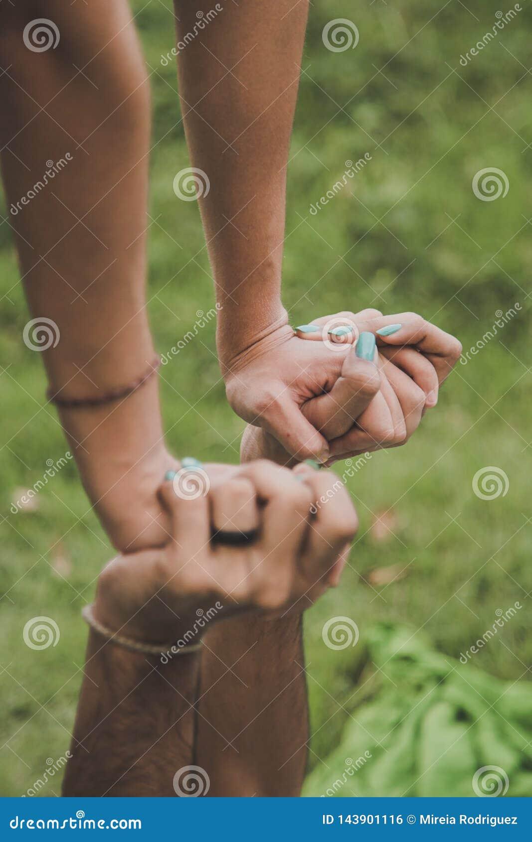 Due mani sono intrecciate in una posizione di equilibrio del acroyoga