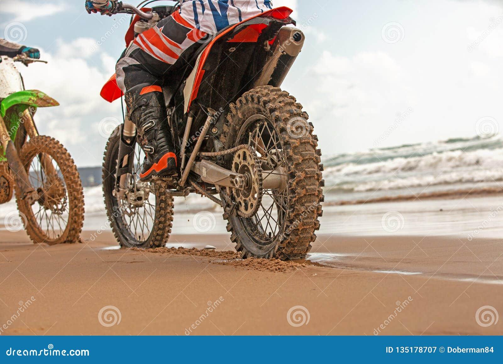 Due motociclisti in un vestito protettivo che si siede sulle motociclette di fronte ad a vicenda davanti al mare