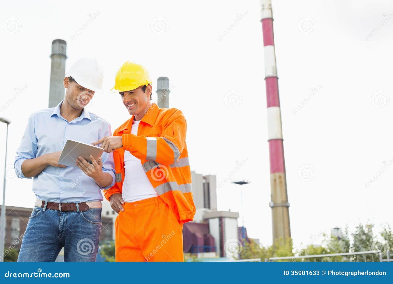 Due muratori che discutono sopra il PC della compressa all industria