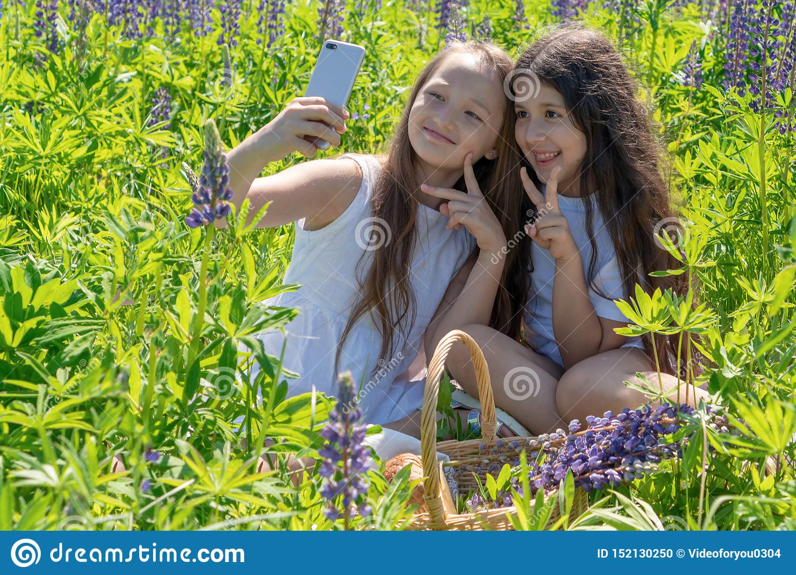 Due neonate fanno il selfie su un telefono fra i fiori in un campo un giorno soleggiato