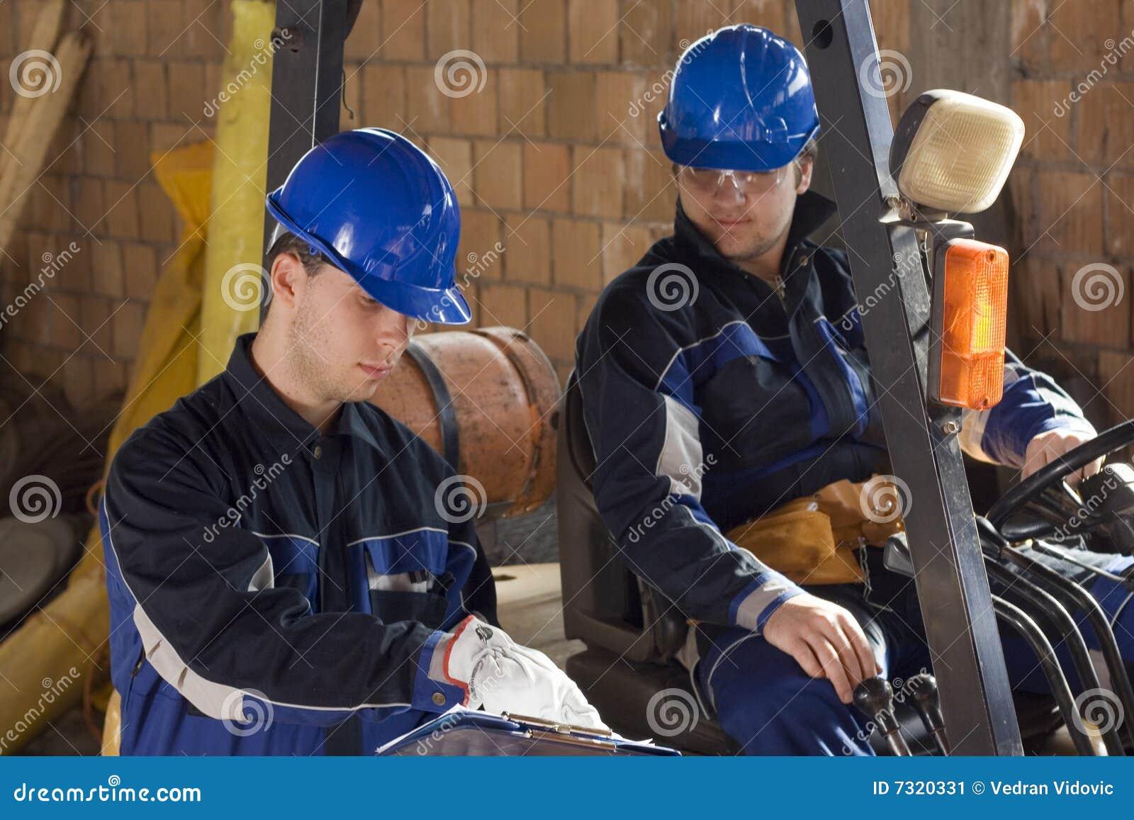 Due operai di costruzione che osservano programma