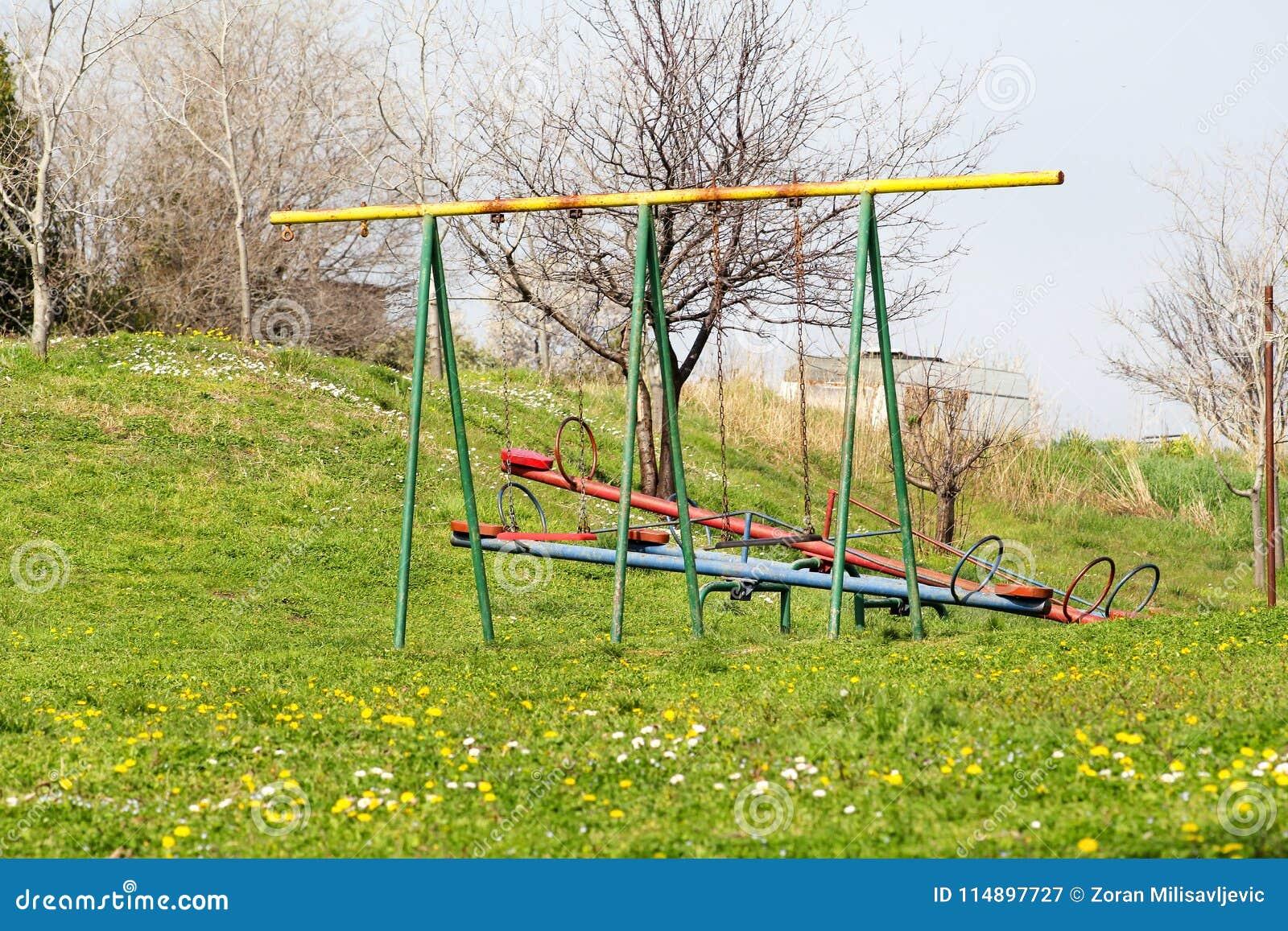 Due oscillazioni e movimenti alternati vuoti dei bambini alle attività del campo da giuoco in parco pubblico/ambiente naturale, l