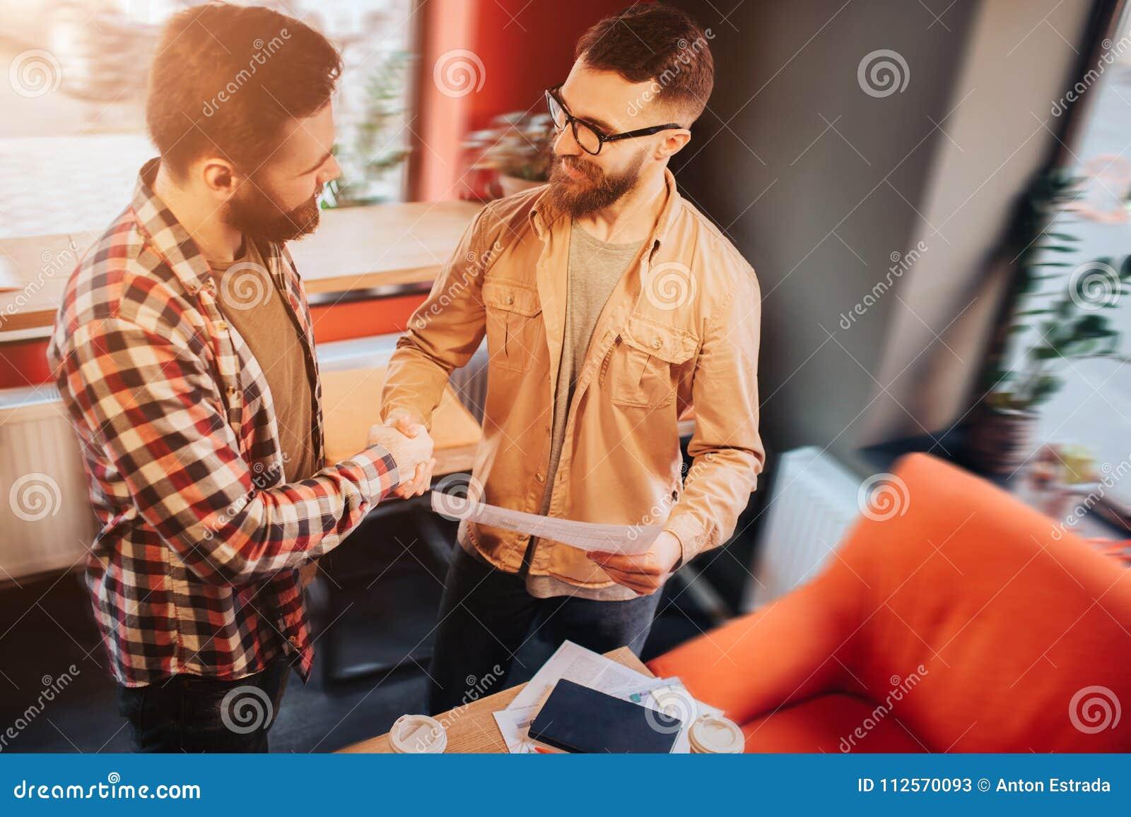 Due pantaloni a vita bassa che indossano l abbigliamento casual che sta in un caffè dello slall e che stringe le loro mani Uno di