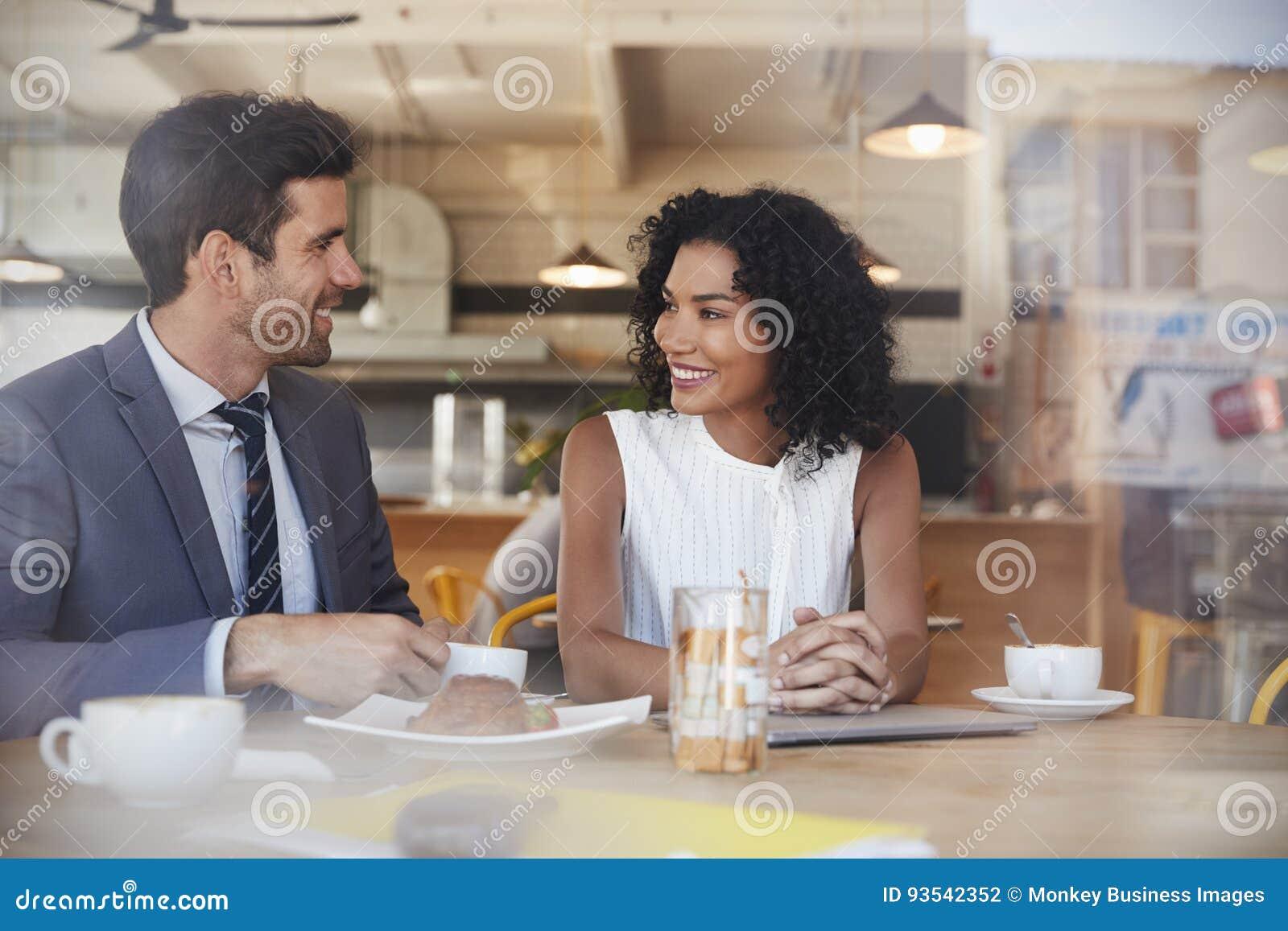 Due persone di affari si incontrano in caffetteria sparata attraverso la finestra