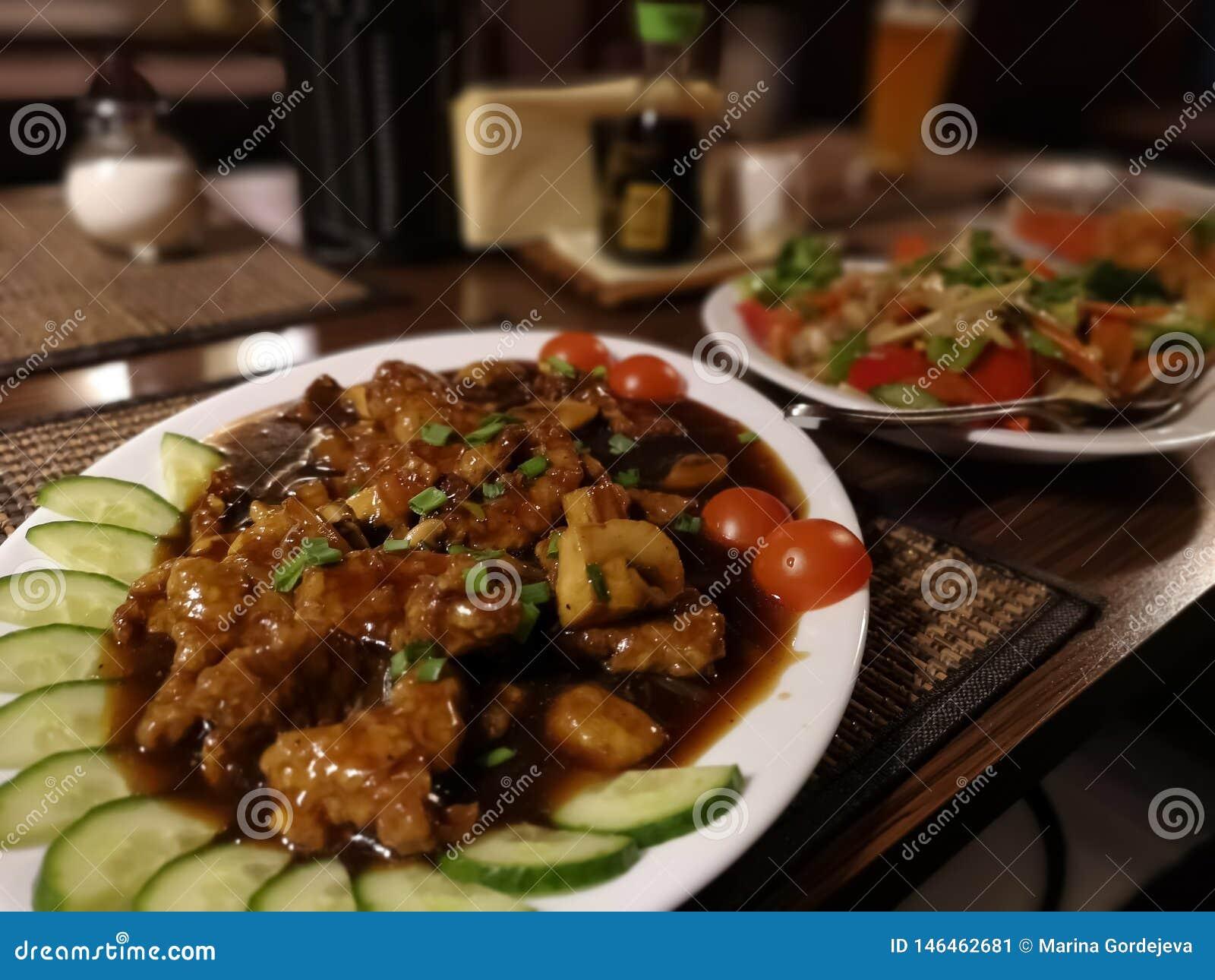 Due piatti orientali con le tagliatelle del manzo, del pollo, dei pomodori, delle carote, del peperone e di riso