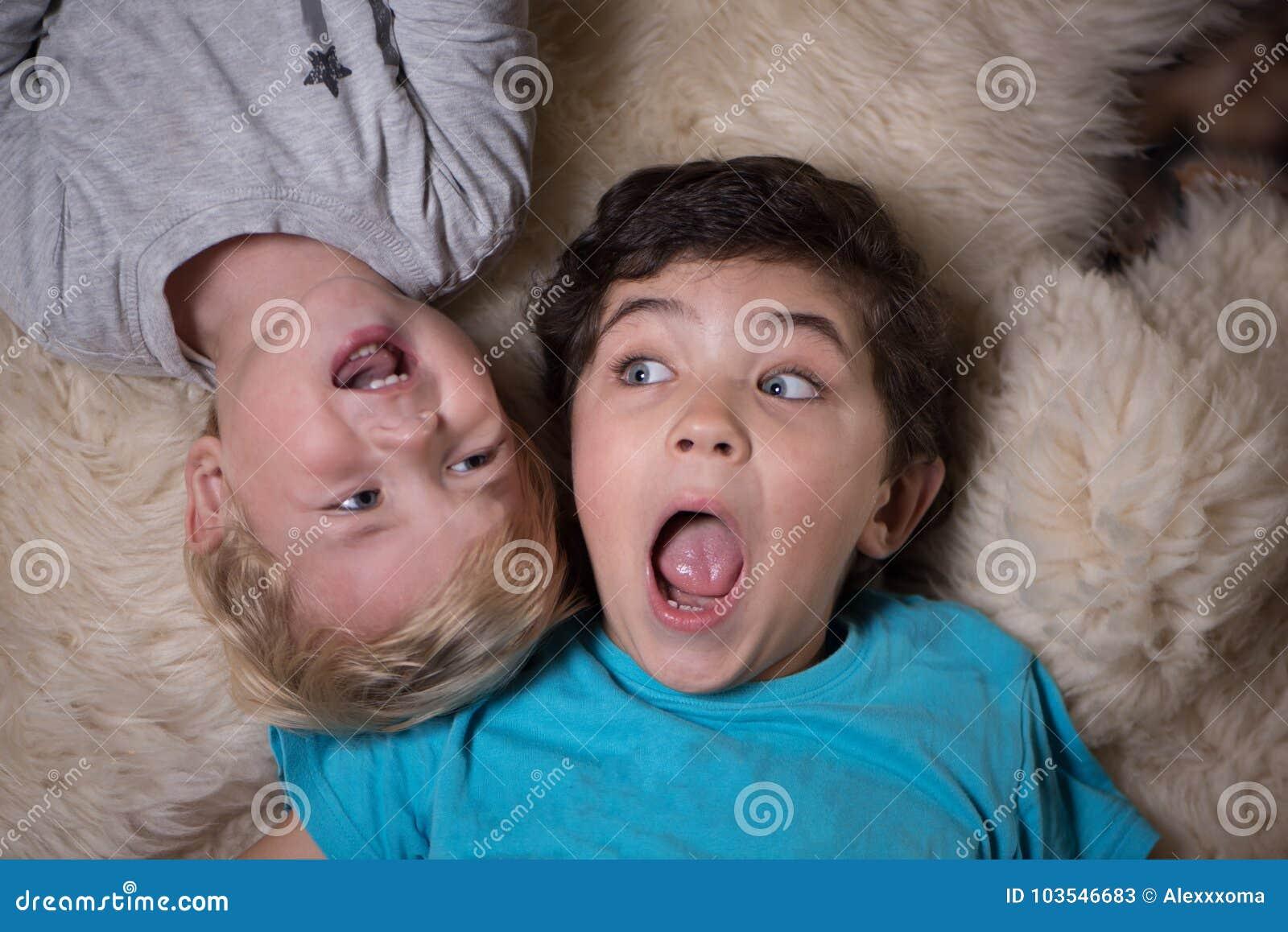 Due piccoli fratelli impertinenti che si trovano sulla pelliccia lanuginosa e che gridano