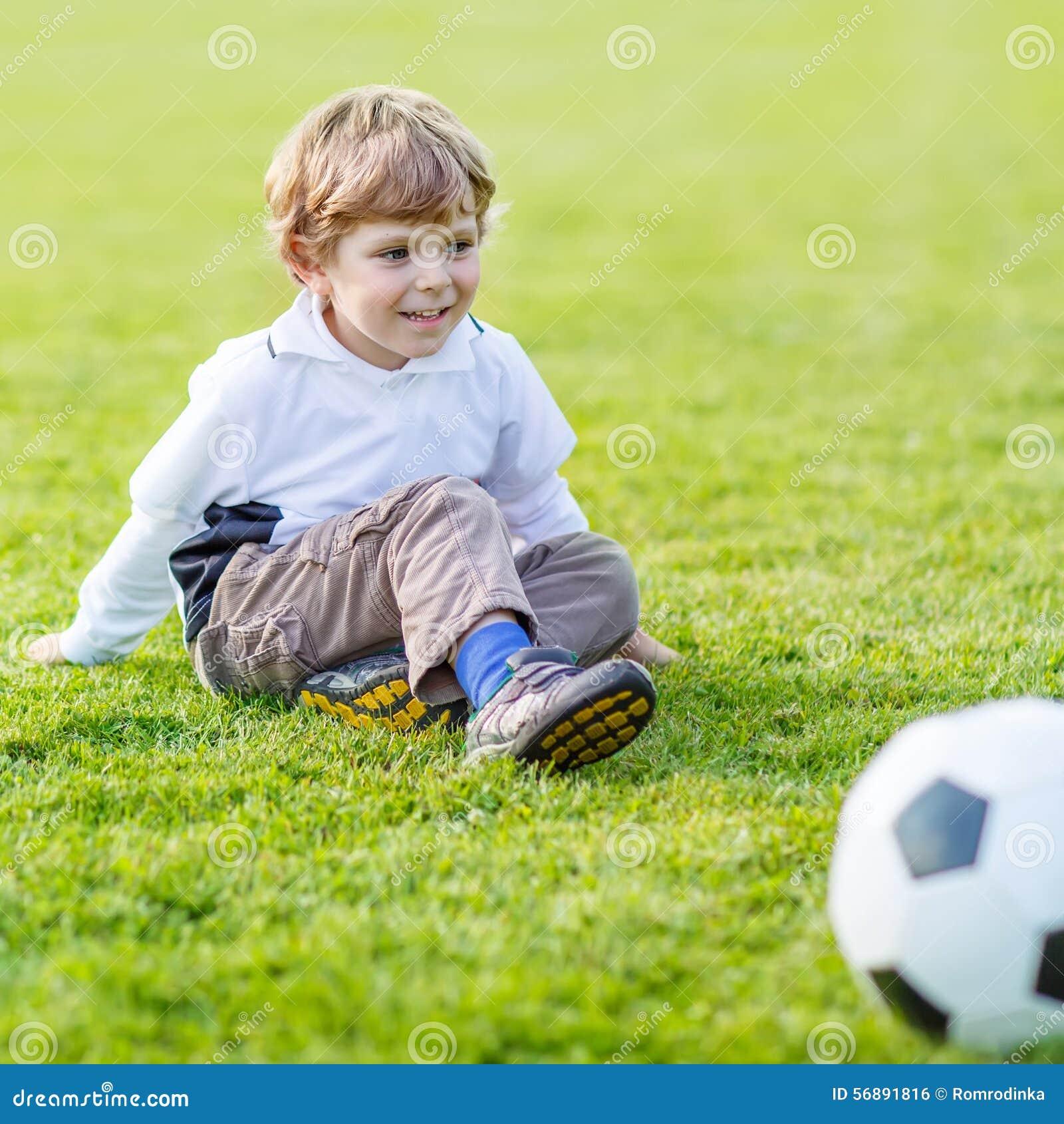 Due piccoli giocar a calcioe e calci dei ragazzi del fratello germano sul campo
