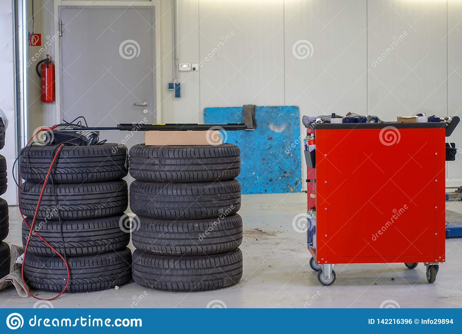 Due pile di gomme di automobile e di carrello portautensili