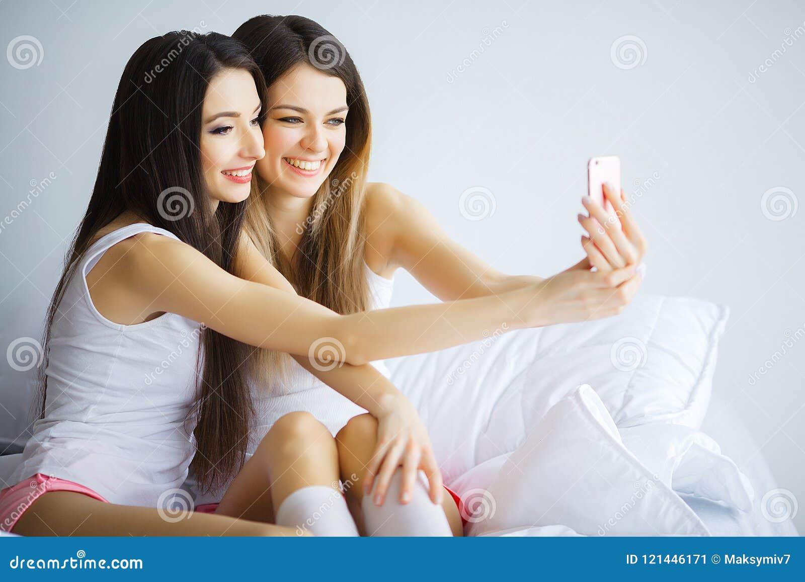 Due ragazze calde che si trovano su un letto che prende una foto se stessi