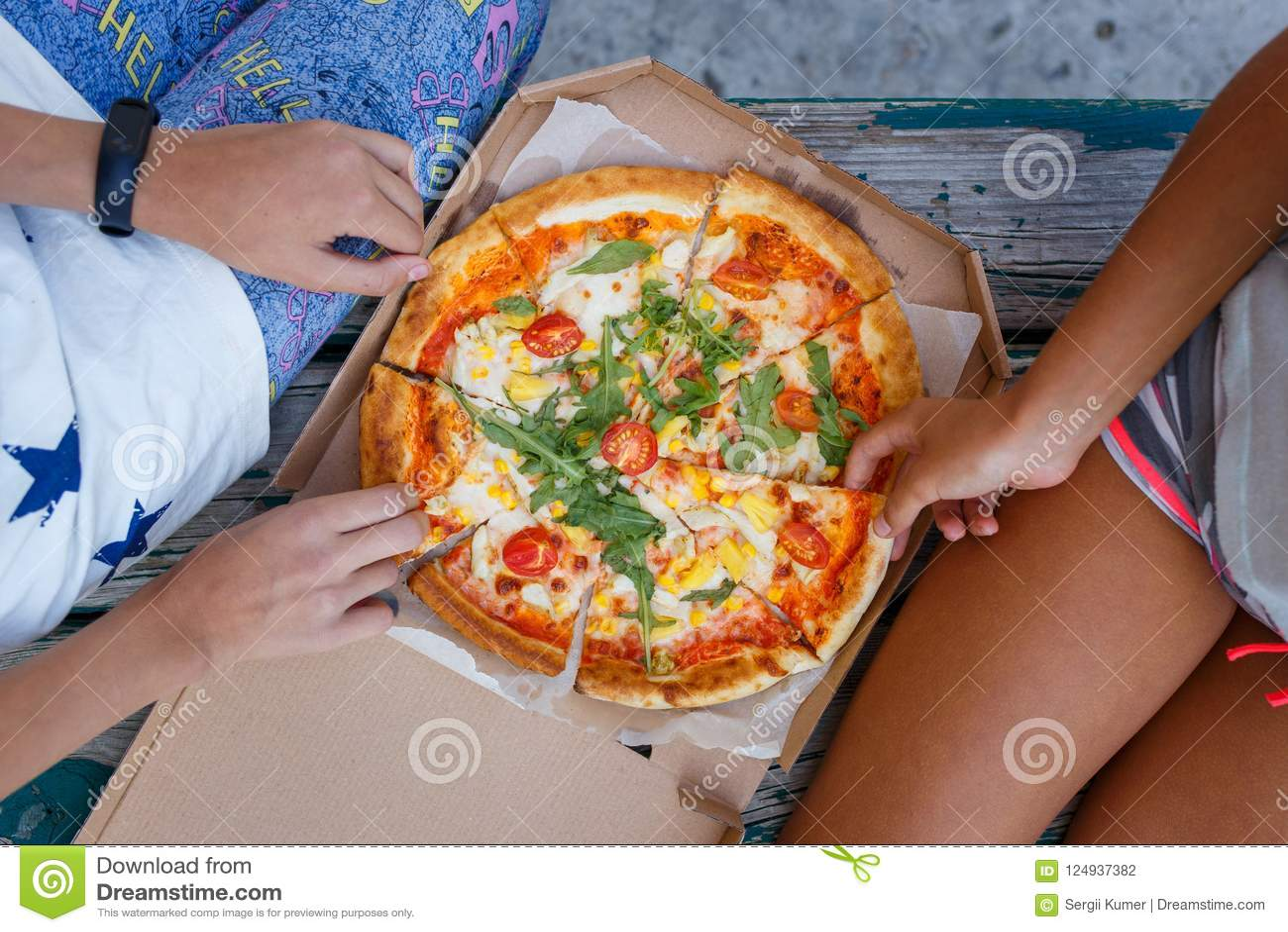 Due ragazze che mangiano la pizza all aperto fanno un picnic insieme