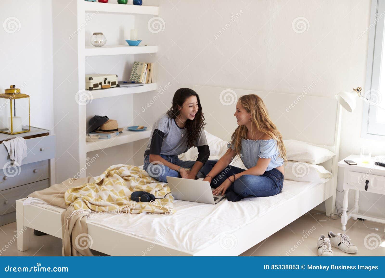 Due ragazze che si siedono sul letto foto stock - A letto con due donne ...