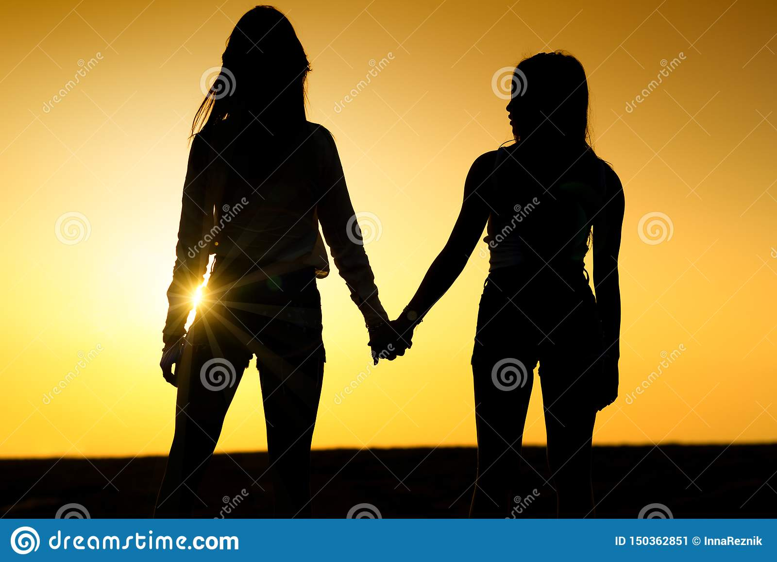 Due ragazze che si tengono mani Coppie delle signore sulla spiaggia
