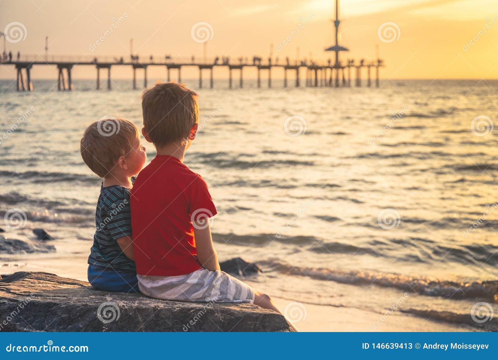 Due ragazzi che si siedono sulla roccia alla spiaggia al tramonto