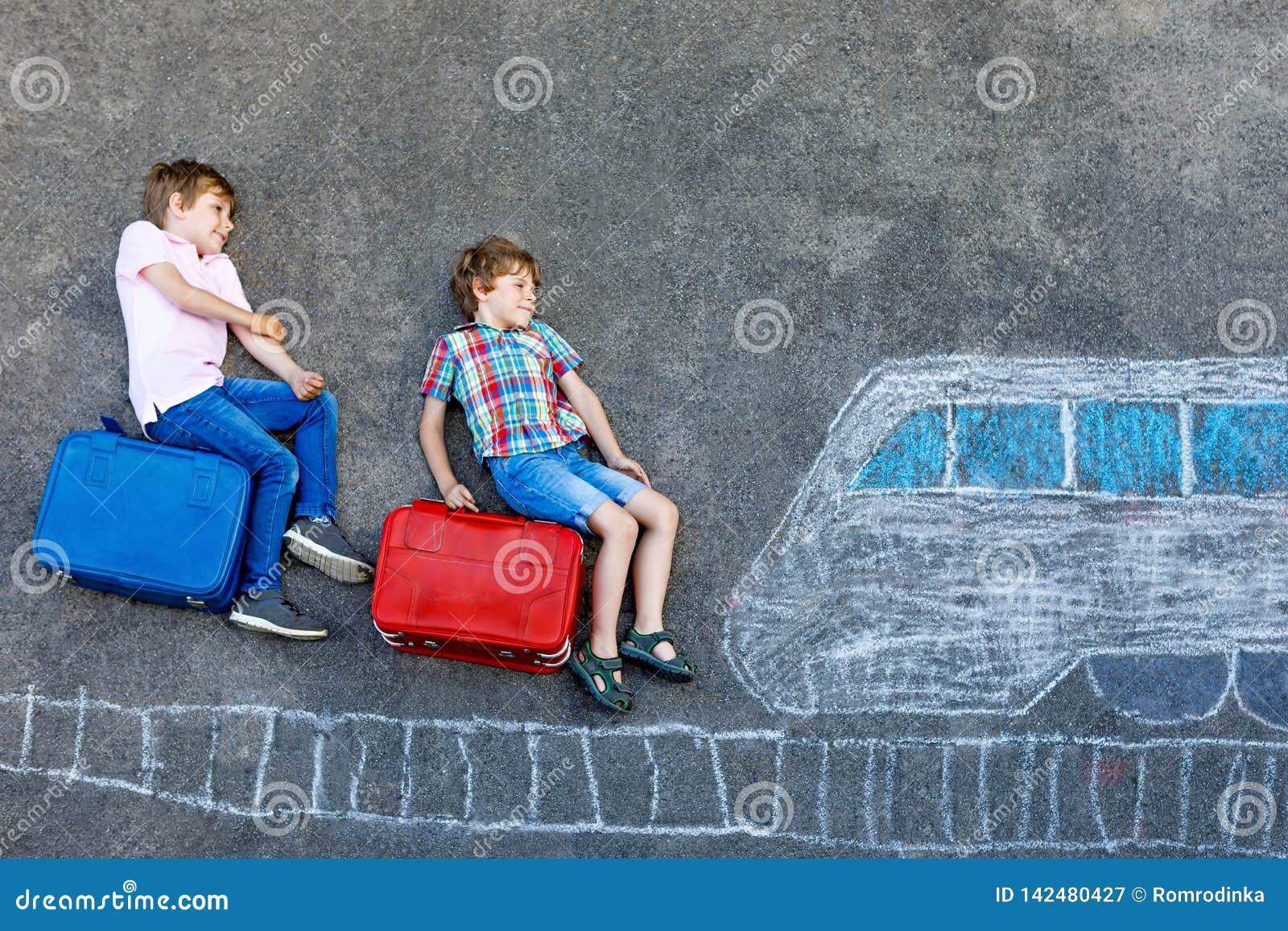 Due ragazzi dei bambini che si divertono con il treno rappresentano il disegno con i gessi variopinti su asfalto Bambini diverten
