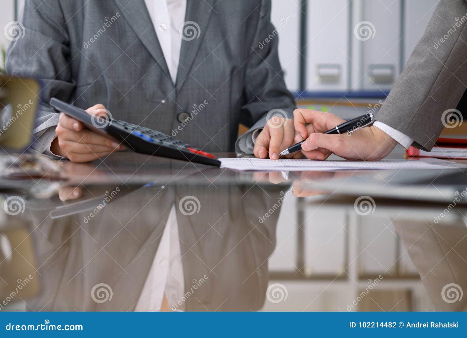 Due ragionieri femminili che controllano rendiconto finanziario o che contano dal reddito del calcolatore per la forma di imposta