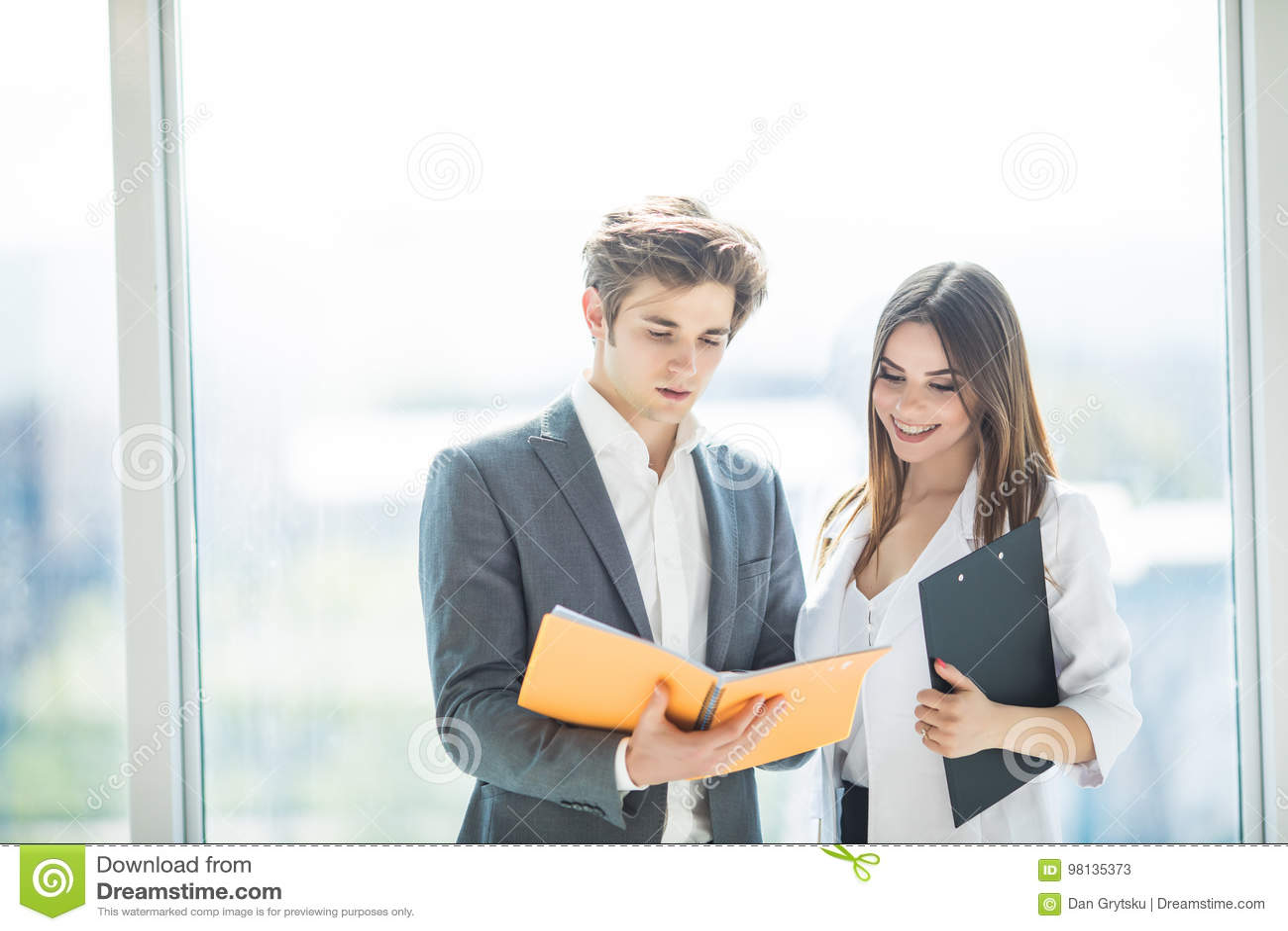 Due responsabili che discutono profitto Gruppo di gente di affari che lavora insieme nell ufficio che discute sopra il taccuino G