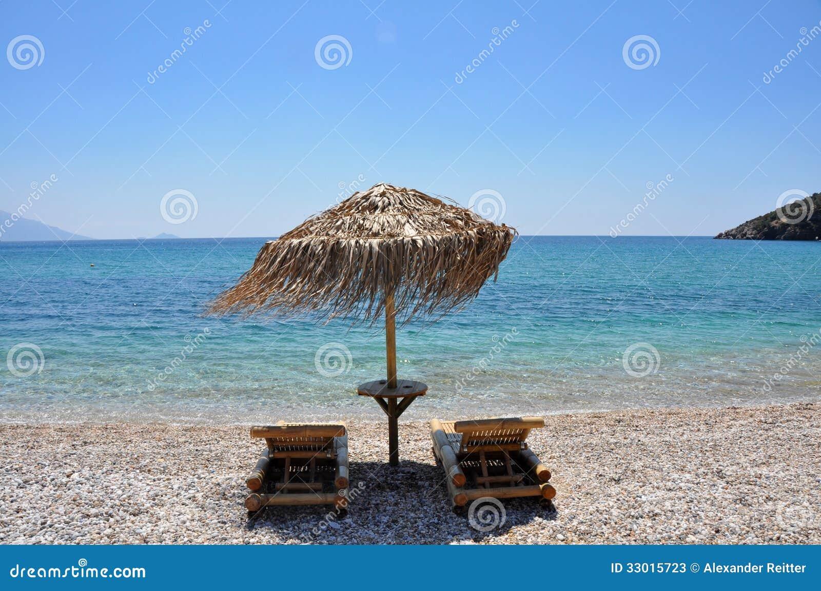 Due sedie del sole sulla spiaggia vuota di samos, grecia ...