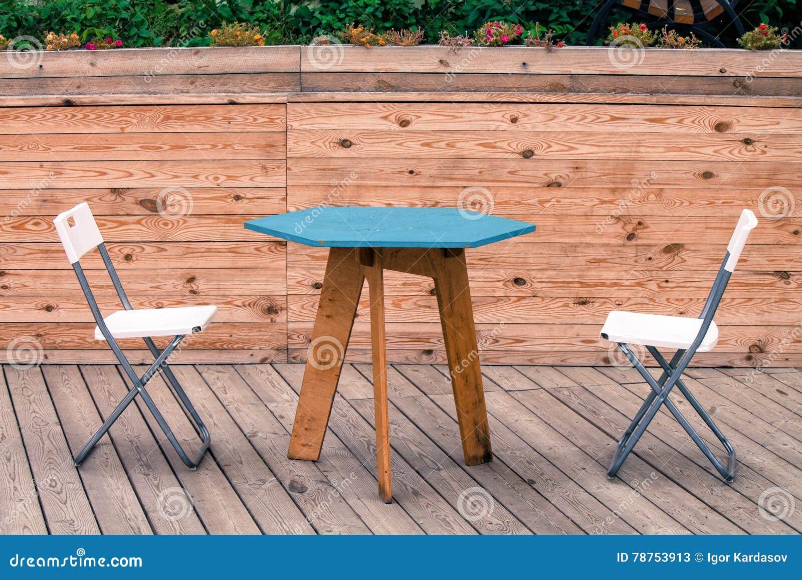 Due sedie moderne bianche vuote con la tavola blu sul pavimento di