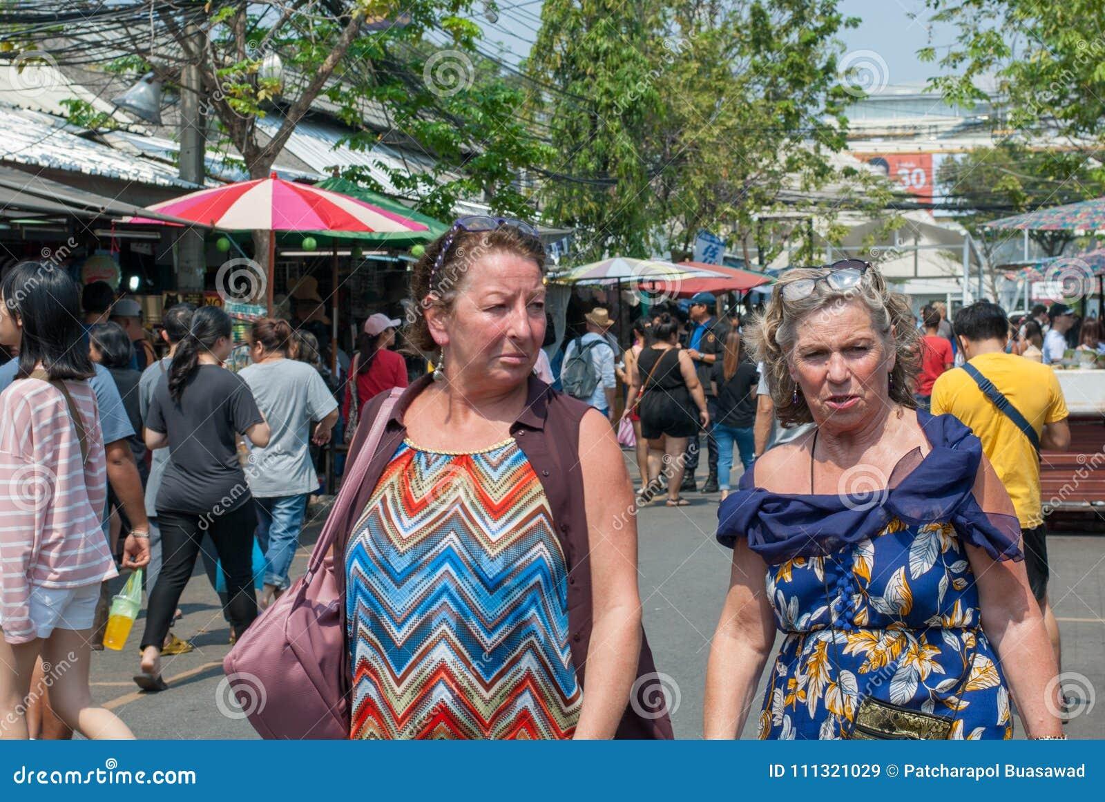 Due signore mature dell occidentale sembrano essere amico che cammina insieme e che parla nel mercato di fine settimana di Chatuc