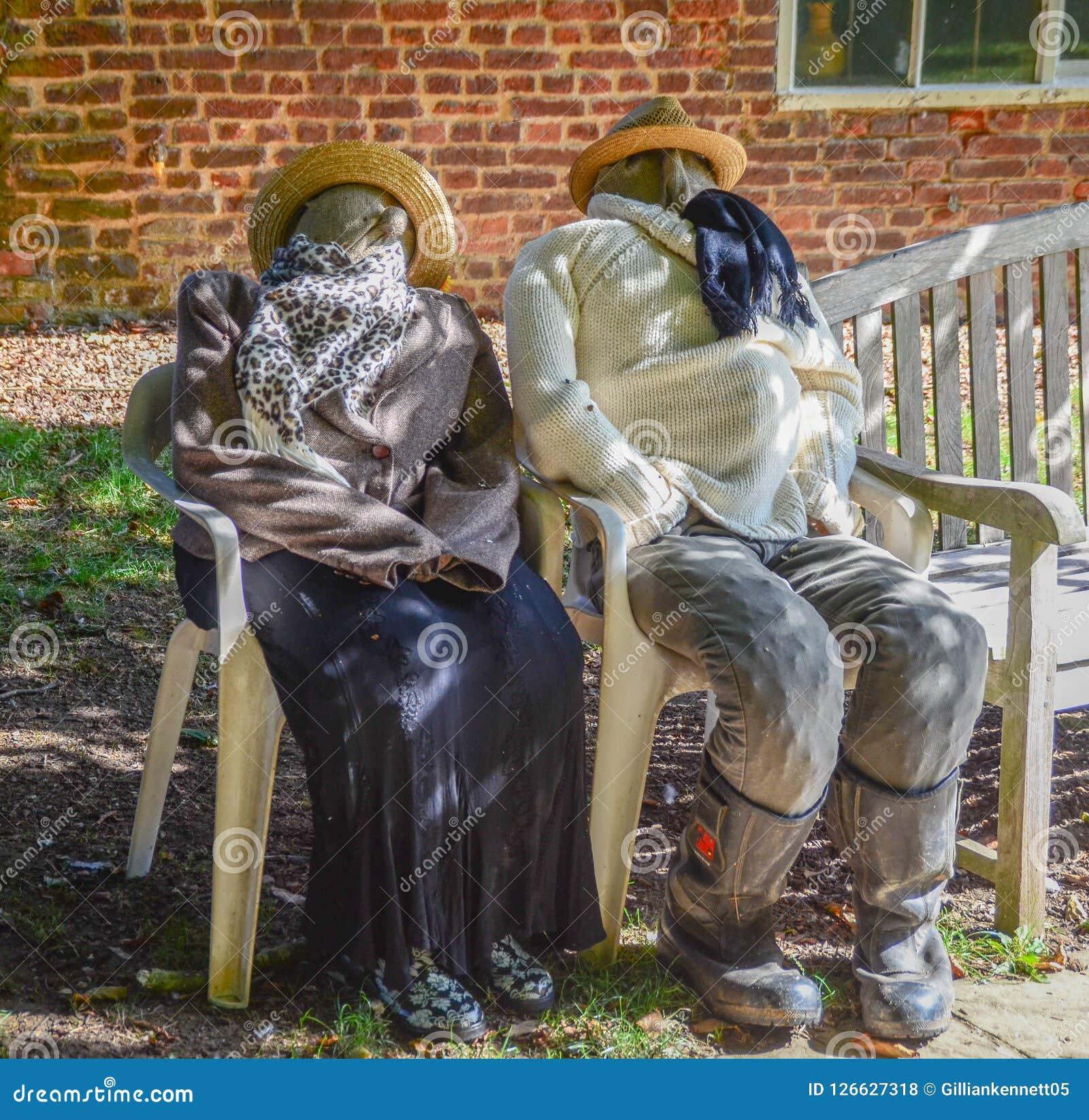 Due spaventapasseri che si siedono sulle sedie fuori Fotografie Stock Libere da Diritti