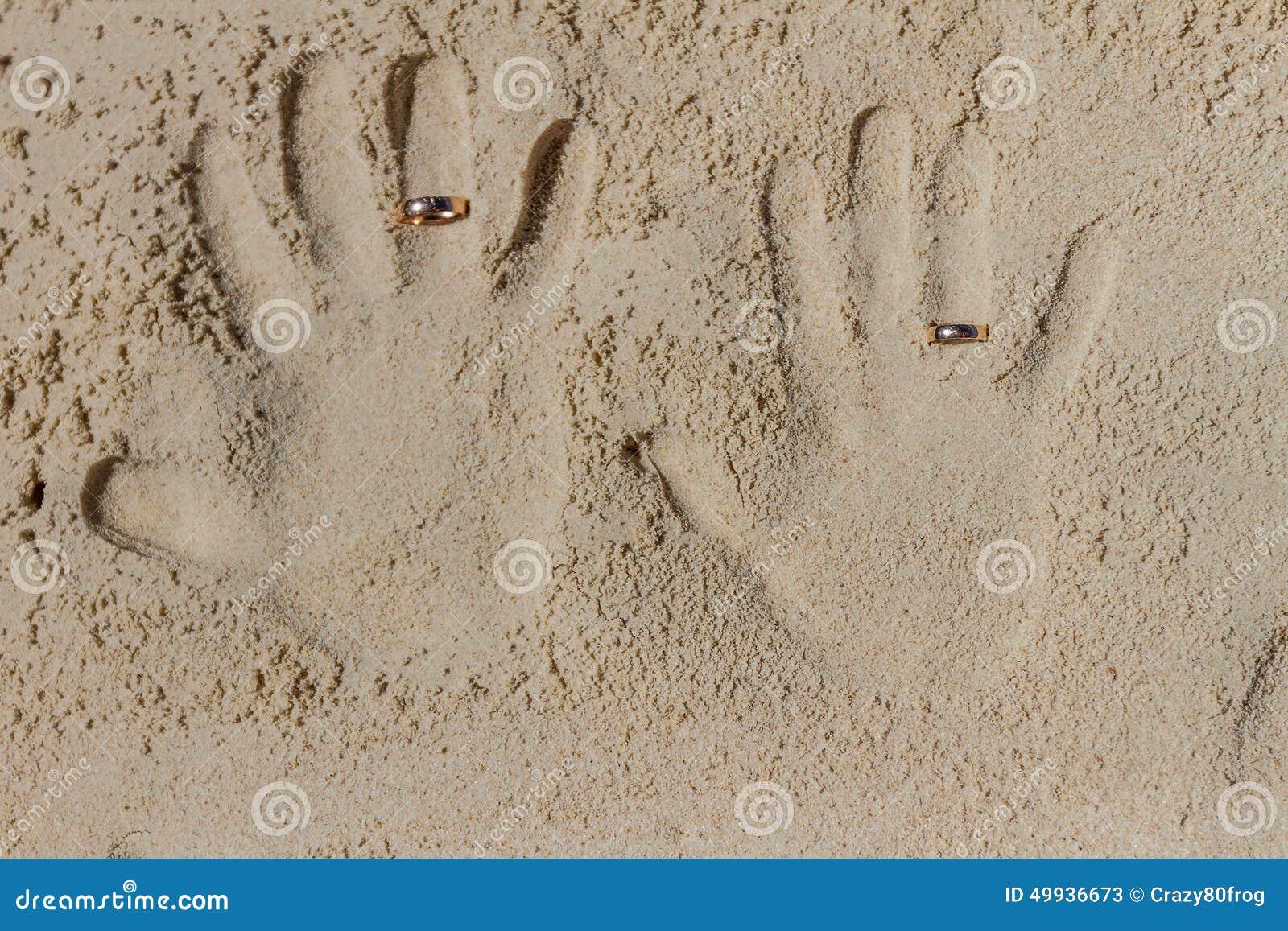 Due stampe della mano con le fedi nuziali sulla spiaggia for Disegni moderni della casa sulla spiaggia