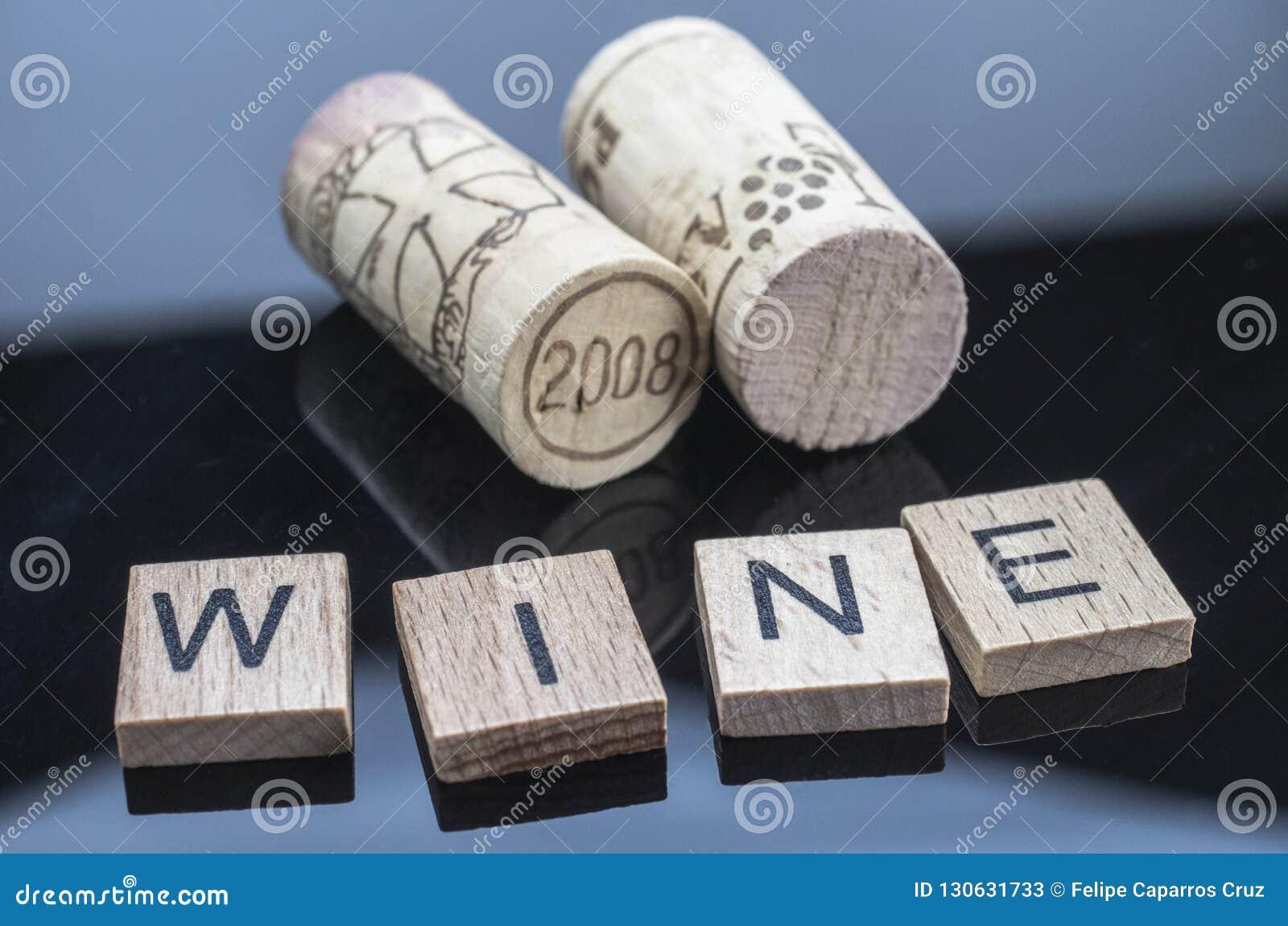 Due sugheri accanto ad alcune lettere di legno con il vino di parola