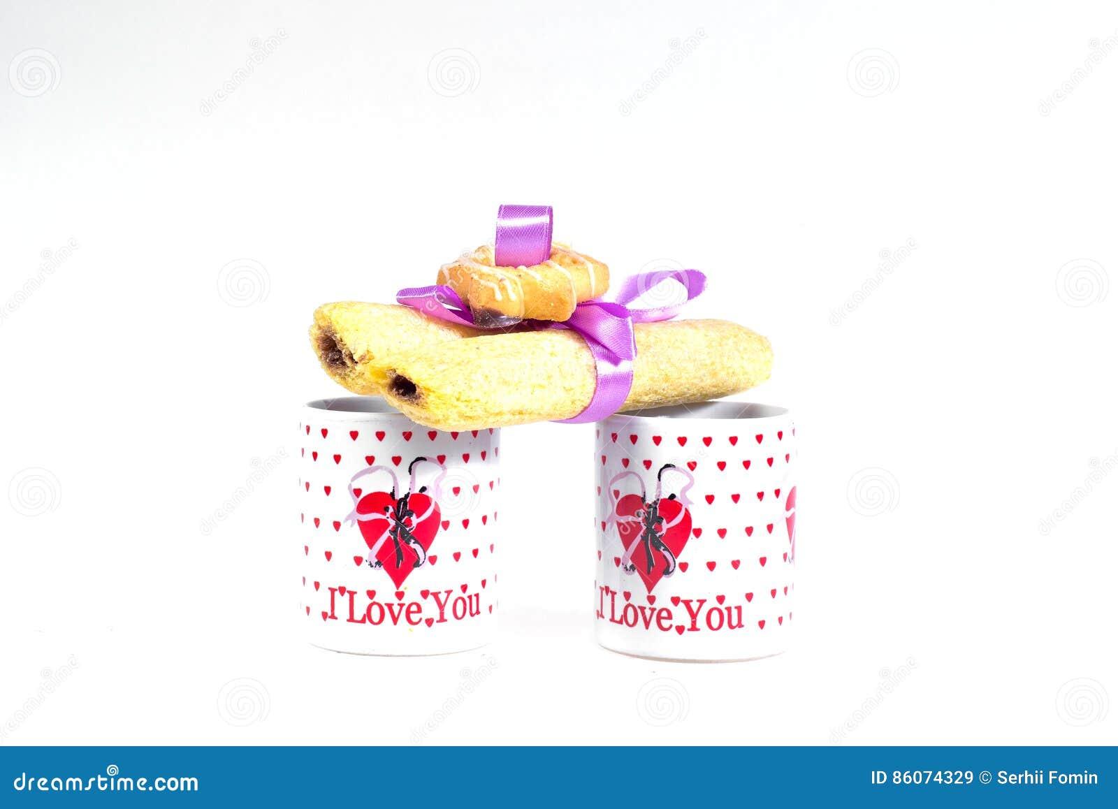 Due tazze di caffè con una dichiarazione di amore e dei biscotti legati con il nastro su un fondo bianco
