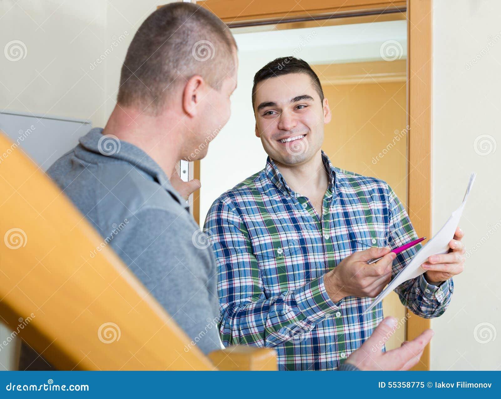 Due uomini al gradino della porta dell appartamento