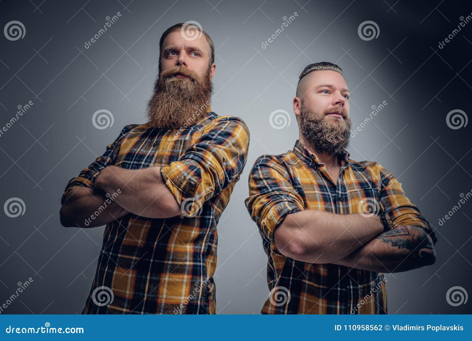 Due uomini barbuti brutali si sono vestiti in una camicia di plaid