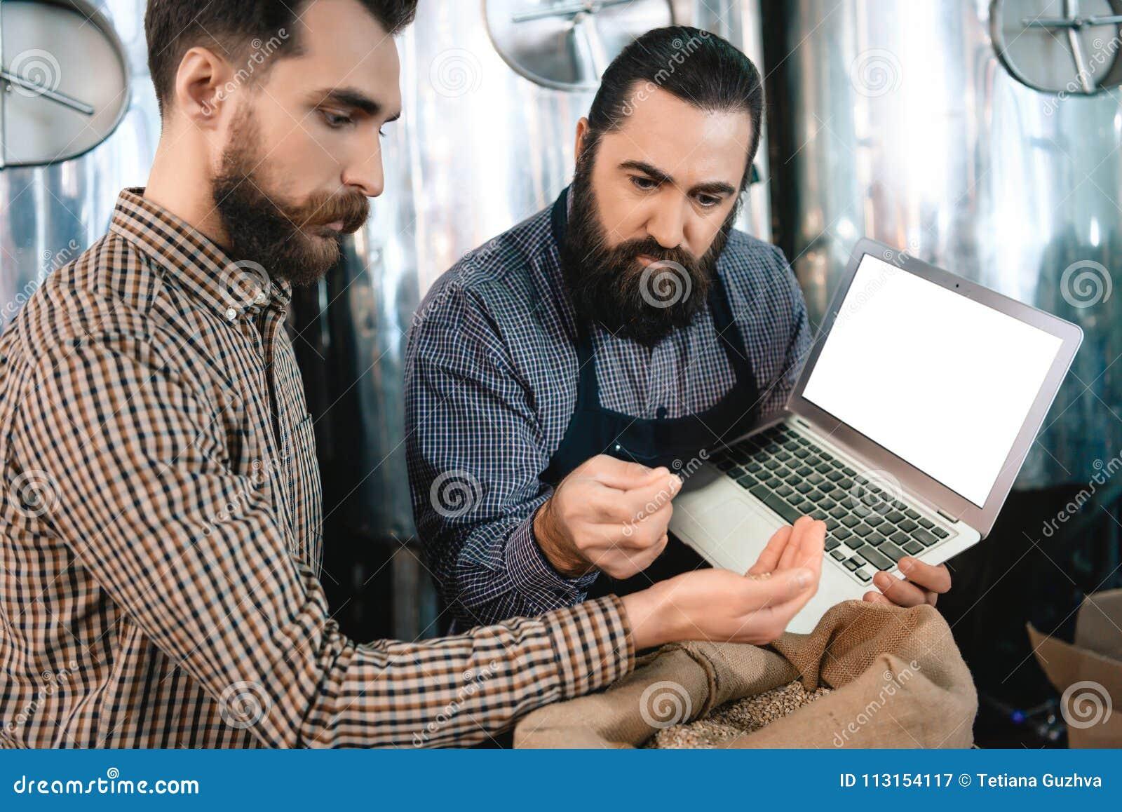 Due uomini barbuti controllano la qualità di malto d orzo mentre in fabbrica di birra Processo di fabbricazione della birra