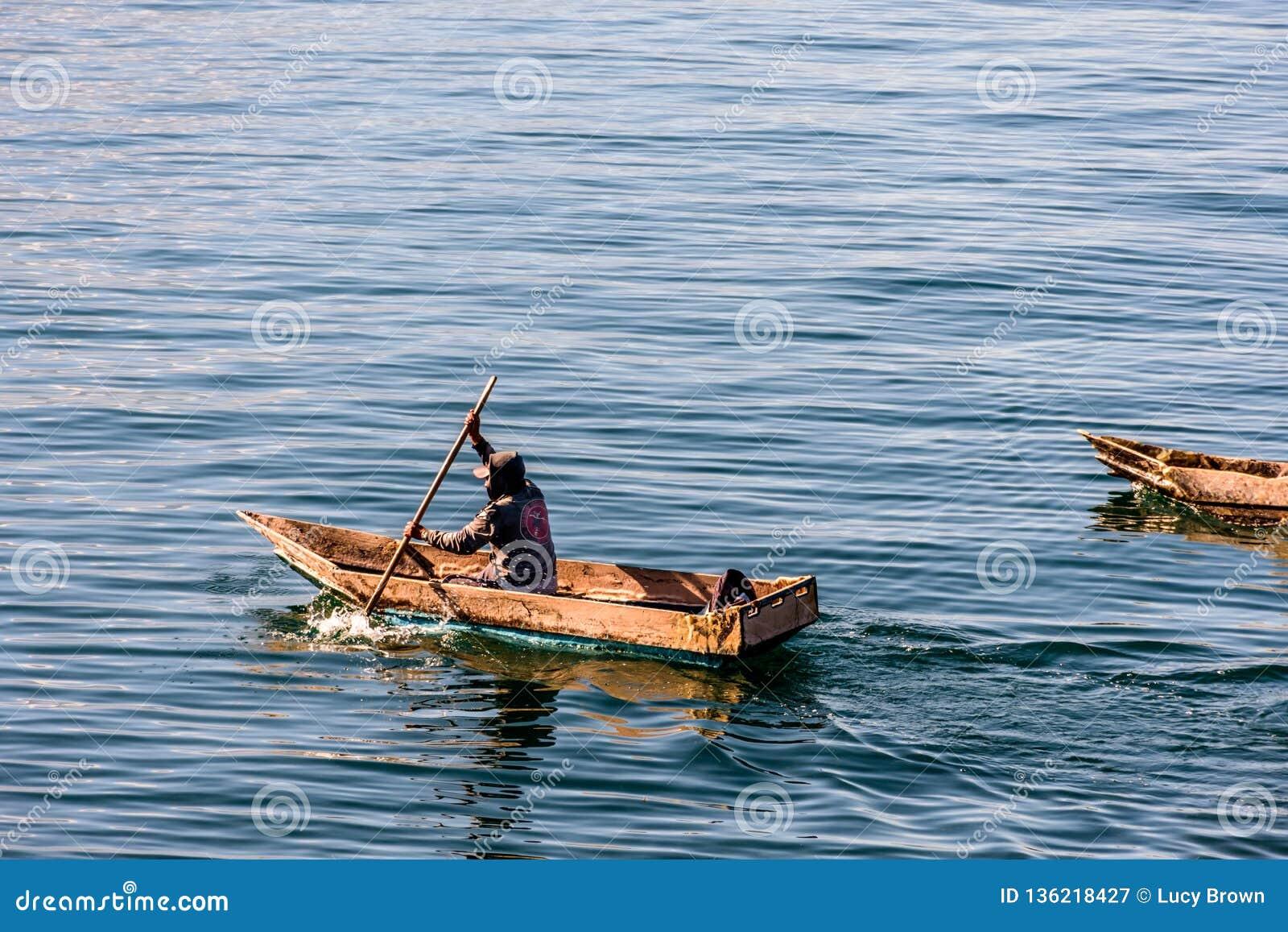 Due uomini in canoe di riparo sul lago Atitlan, Guatemala