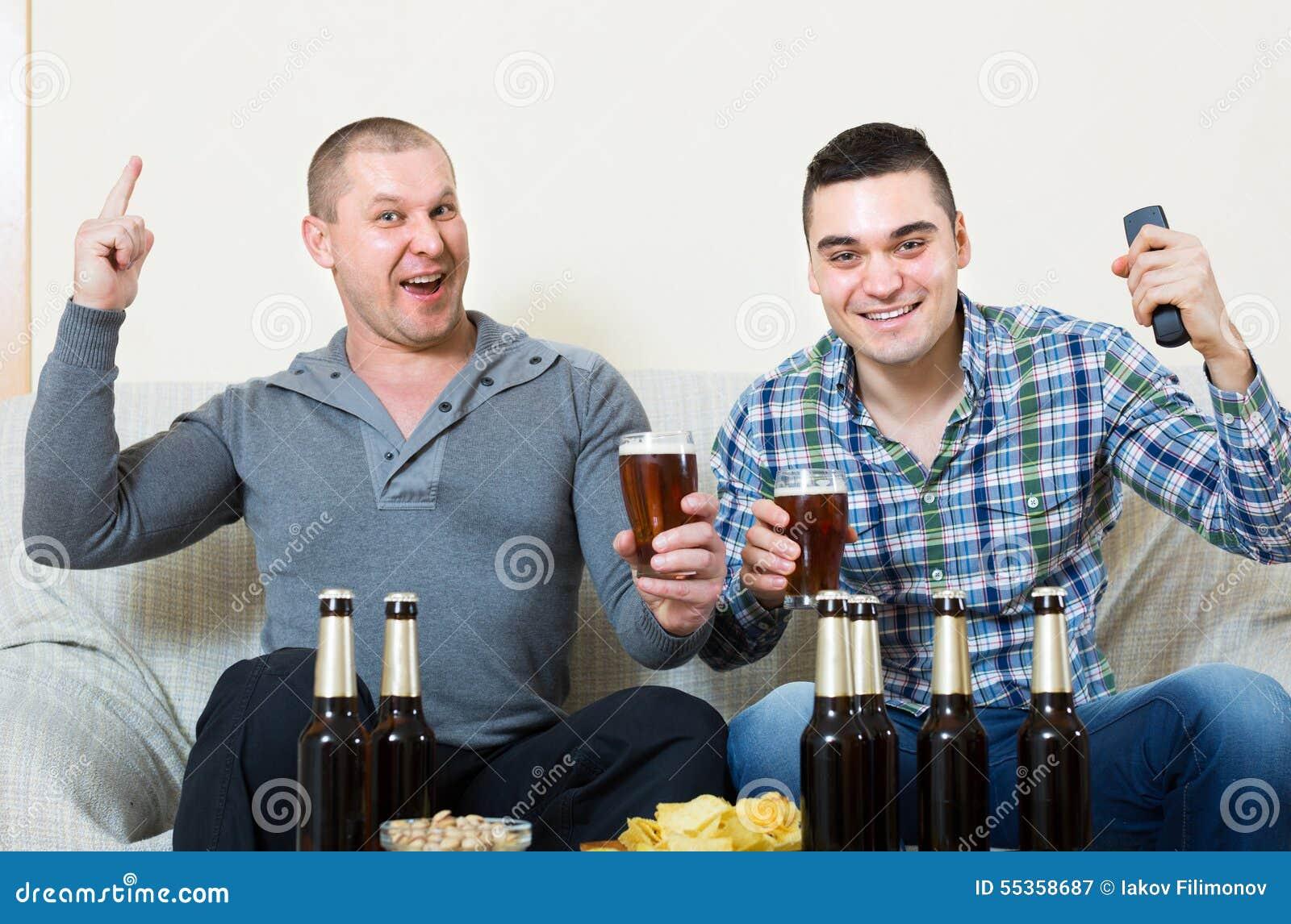 Due uomini che guardano calcio con birra dell interno