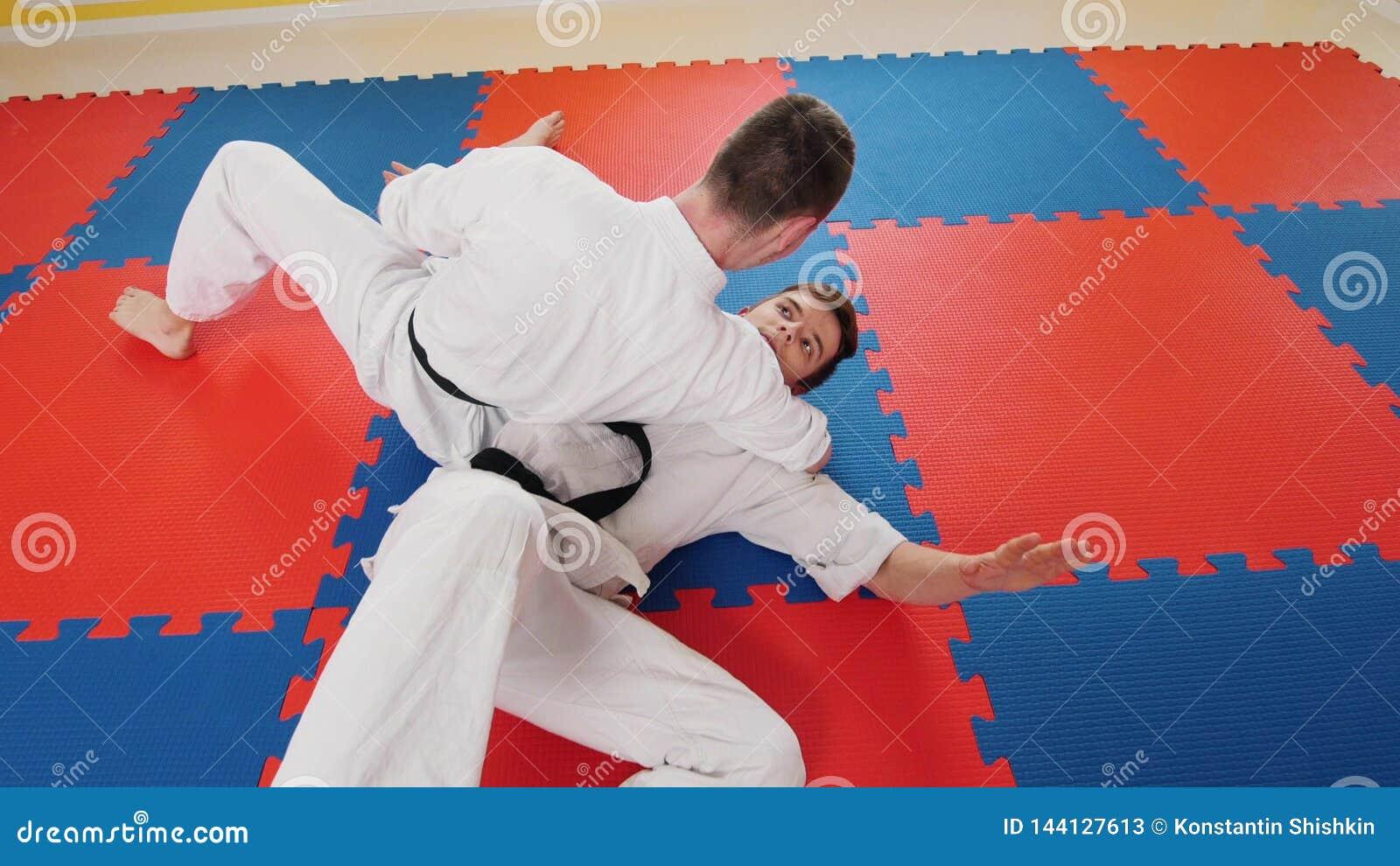 Due uomini che preparano le loro abilit? di aikidi nello studio Un uomo afferra il suo oppositore e lo getta sul pavimento