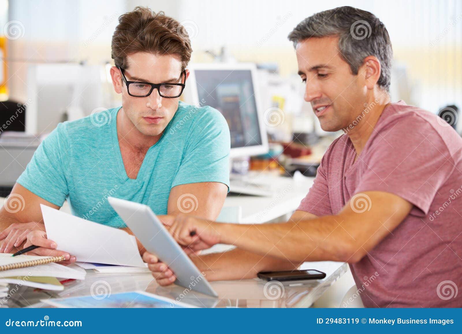 Due uomini che utilizzano il computer della compressa nell ufficio creativo